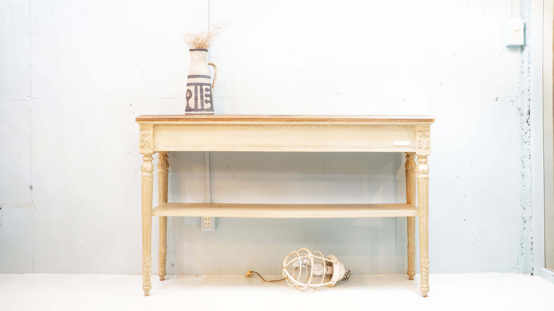 パリに4店舗を構えるインテリアブランド blanc d'ivoire(ブランディボワール)デザイナーのモニクがすべてオリジナルで創る世界はフレンチクラッシックをベースに洗練されたデザインでブランドを確立しています。柔らかく上品な色使いや、アンティーク加工などで温かみをプラスした家具やシャンデリアなど、高級で家族が集うやさしい世界観のライフスタイルを提案しています。こちらのコンソールテーブル、立体的な彫り物は職人のハンドメイド。ペイントもオーガニック自然塗料を使い素材感のあるマットな塗りでアンティークの質感を再現しています。高さが78cmございますので飾り棚には、もちろん作業台としてもお使い頂けるかと思います。奥行きも30cmと日本の間取りにも置きやすく、コンソールとして美しいバランスのデザインです。お探しだった方は、是非この機会にいかがでしょうか。~【東京都杉並区阿佐ヶ谷北アンティークショップ 古一/ZACK高円寺店】 古一では出張無料買取も行っております。杉並区周辺はもちろん、世田谷区・目黒区・武蔵野市・新宿区等の東京近郊のお見積もりも!ビンテージ家具・インテリア雑貨・ランプ・USED品・ リサイクルなら古一へ~