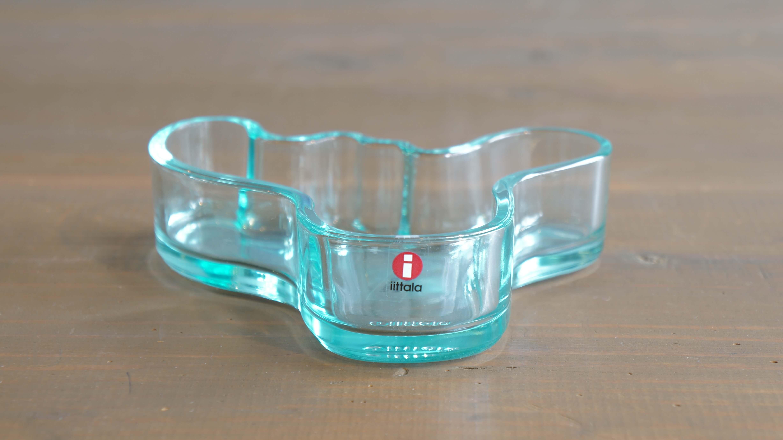"""フィンランドを代表する、現代建築の巨匠、アルヴァ・アアルトが1936年にイッタラから発表した""""アルヴァ・アアルト ベース""""。フィンランドの湖からインスピレーションを受けて作られたという独特な形のガラス器は イッタラで最も有名とされるほど、世界中で愛されています。こちらはそのアアルトベースのオリジナルの形をそっくりそのままサイズダウンしたボウル。器として使うのはもちろん、小物入れとしてもお使いいただけます。使い方次第で様々な顔をみせてくれそうです。カラーは、これもまたフィンランドの湖が目に浮かぶような美しいウォーターグリーン。フィンランドの自然にボウルの形がくり抜かれたユニークな元箱もついています。そして、こちらのカラーのボウルは現在廃盤となっているレアなアイテムです。使わないときでも、その場に置いておくだけでオブジェのようになるアアルトのデザイン。ぜひ、食卓やインテリアにいかがでしょうか♪~【東京都杉並区阿佐ヶ谷北アンティークショップ 古一/ZACK高円寺店】 古一/ふるいちでは出張無料買取も行っております。杉並区周辺はもちろん、世田谷区・目黒区・武蔵野市・新宿区等の東京近郊のお見積もりも!ビンテージ家具・インテリア雑貨・ランプ・USED品・ リサイクルなら古一/フルイチへ~"""
