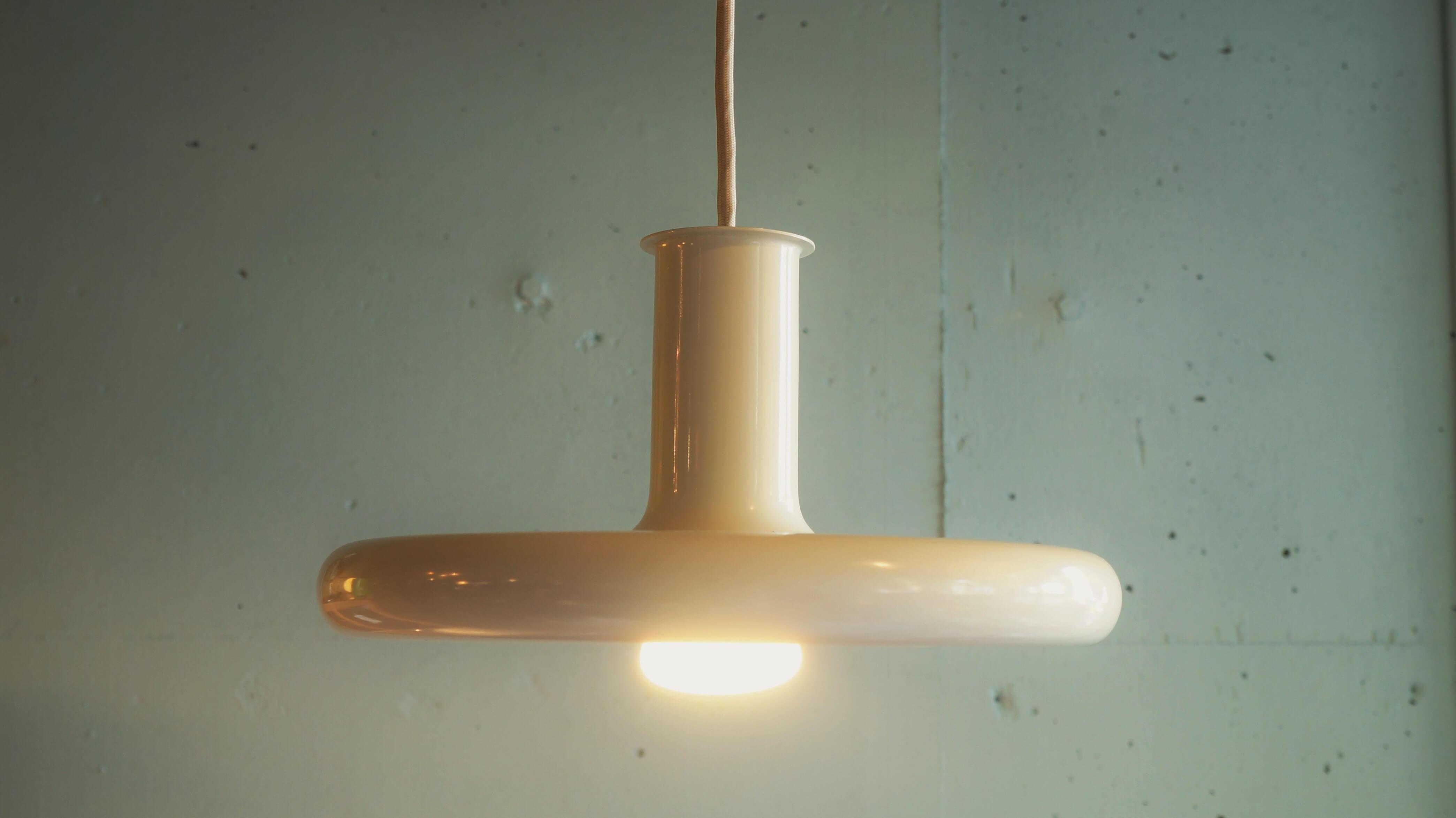 """ミッドセンチュリー北欧デザインを代表するデンマークの老舗照明メーカー、Fog&Morup/フォグ&モーフのペンダントライト""""Optima/オプティマ""""。Fog&Morup社は1904年にデンマークに設立され、1906年からコペンハーゲンを拠点に、照明メーカー、ディーラーとして活動の場を広げていきます。1960年代には、Jo Hammerborg/ヨー・ハーマボーのデザインが脚光を浴び、ルイスポールセンと並び北欧モダンデザインを牽引しました。その後、長年チーフディレクターを務めたヨー・ハーマボーの引退により、1980年にブランドは消滅してしまいました。そのため、手に入るものは全てヴィンテージ品となっています。Fog&Morup社はヨー・ハーマボーのデザインが有名ですが、こちらのHans Due/ハンス・デューデザインのト""""Optima/オプティマ""""もブランドのイメージを決定づけた名作と言われています。ハンス・デューはデンマーク出身の工業デザイナー、写真家です。 1974年に自身の会社Due Design A / Sを設立し、多くの広告会社や デザイン会社でアートディレクションとグラフィックデザインを担当しました。こちらの""""オプティマ""""は1973年に発表され、現在でも同氏の代表作として知られています。円盤のようなフォルムですっきりとした無駄のないデザイン。当時は同じデンマーク出身のデザイナー、ヴェルナー・パントンなどのプロダクトデザインにも見られるような、スペースエイジやアトミックエイジと言われた近未来的、宇宙的なデザインが人気を博していました。この""""オプティマ""""もそんな雰囲気が漂う、70年代特有のユニークなデザインとなっています。シェードはアルミでできており、白くペイントされています。場所を選ばない、シンプルでコンパクトなサイズ感。どんな空間にも合わせやすく、さりげなく北欧の空気を演出してくれるようなランプを ぜひいかがでしょうか♪~【東京都杉並区阿佐ヶ谷北アンティークショップ 古一/ZACK高円寺店】 古一/ふるいちでは出張無料買取も行っております。杉並区周辺はもちろん、世田谷区・目黒区・武蔵野市・新宿区等の東京近郊のお見積もりも!ビンテージ家具・インテリア雑貨・ランプ・USED品・ リサイクルなら古一/フルイチへ~"""