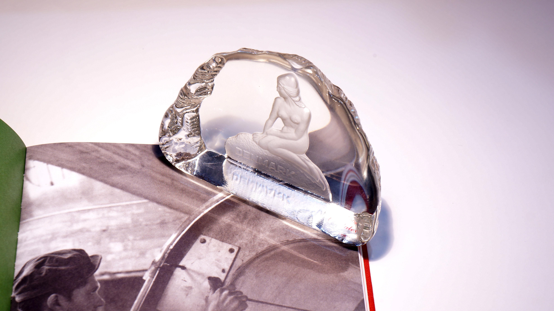 1945年にボヘミア地方にあった55個の小さなガラス工場が集まり、国営のガラス工場が生まれ、1967年にガラス作りが盛んなノヴィーボール市のいくつかの工場が参加し発展、1974年に会社を設立。高品質で実用的な同社製品の90%がヨーロッパをはじめとする世界70ヶ国に輸出されている Crystalex/クリスタレックス社。こちらのお品物は、大変珍しくスウェーデンでハンドメイド製作が行われ、デンマークのお土産品として販売されていた物になります。デンマーク・コペンハーゲンにあり、観光名所として知られるハンス・クリスチャン・アンデルセンの童話・人魚姫のブロンズ像がモチーフのペーパーウェイトです。光りの屈折で様々な表情を見せてくれるアートガラスです。北欧インテリアのお部屋、書斎などに是非いかがでしょうか~【東京都杉並区阿佐ヶ谷北アンティークショップ 古一/ZACK高円寺店】 古一/ふるいちでは出張無料買取も行っております。杉並区周辺はもちろん、世田谷区・目黒区・武蔵野市・新宿区等の東京近郊のお見積もりも!ビンテージ家具・インテリア雑貨・ランプ・USED品・ リサイクルなら古一/フルイチへ~