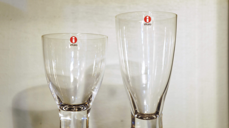 """北欧デザインを象徴するフィンランドのテーブルウェアブランドiittalaを代表するグラスシリーズ""""タピオ""""のゴブレットとレッドワインのセット。フィンランドを代表するデザイナー、タピオ・ヴィルカラがデザインしました。タピオ・ヴィルカラは現代デザインのレジェンドのひとりとして、世界的に知られているデザイナー・彫刻家。1946年からイッタラのデザイナーとなり、数多くの作品を手掛けました。1940年代から1980年代には400を超えるグラスをデザイン。ほかにもカトラリーやテーブルウェア、家具、ケチャップの容器、紙幣にいたるまで、さまざまな芸術的な作品を残しています。タピオシリーズの特徴である台座部分の気泡(バブル)は、熱いガラスに濡れた木のスティックを差し込み、中で蒸発する水分により空気の膜ができることで作られます。柔らかく、なだらかなラインのタピオのグラスは全体の形が光と影によって美しい視覚効果を与えてくれます。美しいデザインだけでなく、持ちやすい適度な重さや、口当たりの良い機能性も兼ねそろえたグラスです。こちらは2個セットになっていますので、ご夫婦やカップルでお使いいただくのもよし、また、飲み物で使い分けるのもおススメです。美しさと機能性を兼ねそろえたグラスで一杯いかがですか♪~【東京都杉並区阿佐ヶ谷北アンティークショップ 古一/ZACK高円寺店】 古一/ふるいちでは出張無料買取も行っております。杉並区周辺はもちろん、世田谷区・目黒区・武蔵野市・新宿区等の東京近郊のお見積もりも!ビンテージ家具・インテリア雑貨・ランプ・USED品・ リサイクルなら古一/フルイチへ~"""