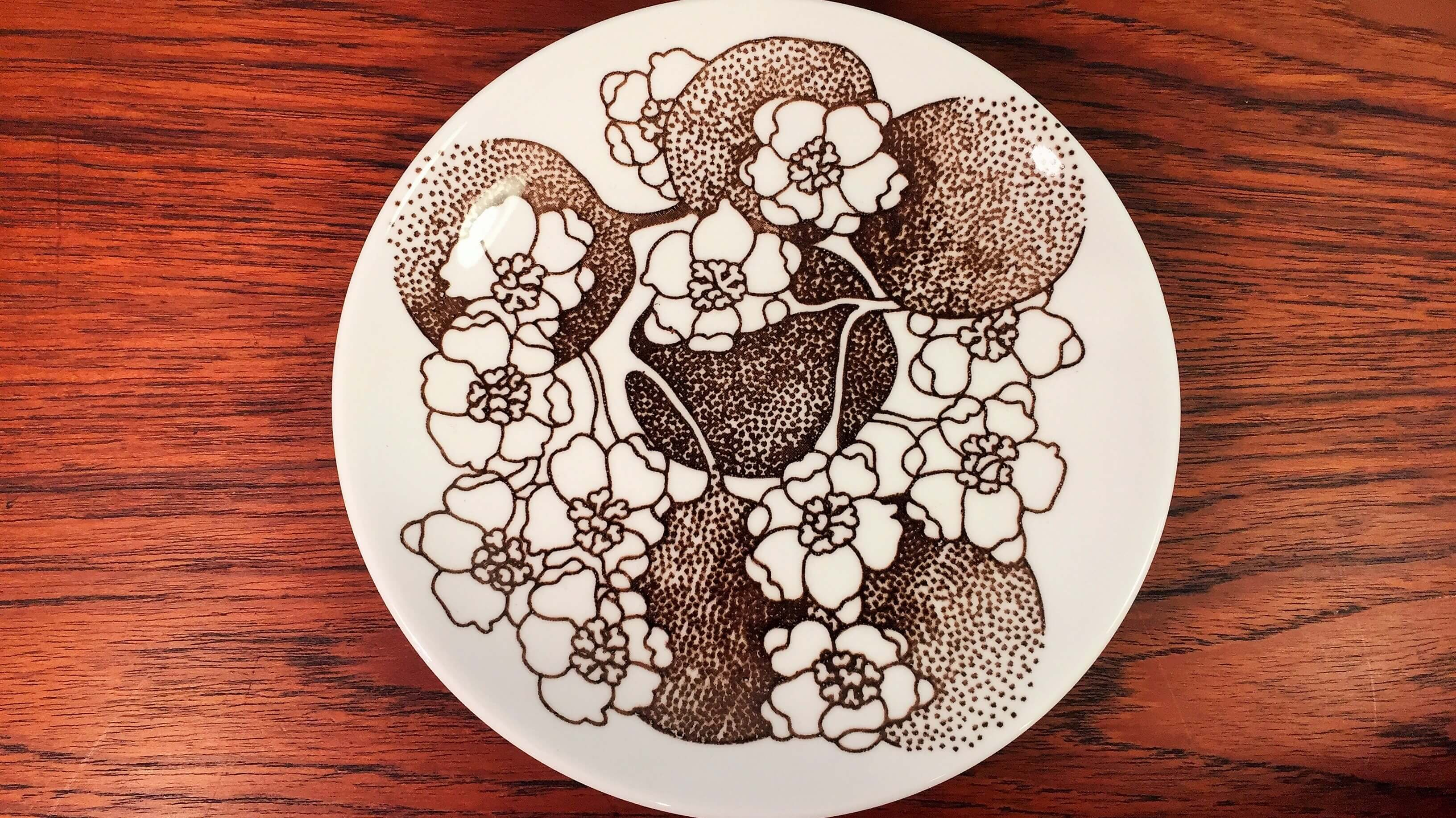 """スウェーデンの陶器ブランド、グスタフスベリの""""エマ""""シリーズのプレート。 フォルムデザインはグスタフスベリを代表する天才デザイナー、スティグ・リンドベリ。 デコレートデザインはアザラシなどの動物をモチーフにしたオブジェでも有名なパウル・ホフ。 """"エマ""""は白地にブラウン一色でりんごとその花が大胆に描かれており、 華やかさと、上品で落ち着いた雰囲気のあるシリーズです。 17cmのプレートはケーキやフルーツ、パンなどをのせたりと、 日常使いにちょうどいい大きさです。 ティータイムや朝食のお供にぜひいかがでしょうか♪ ~【東京都杉並区阿佐ヶ谷北アンティークショップ 古一/ZACK高円寺店】 古一/ふるいちでは出張無料買取も行っております。杉並区周辺はもちろん、世田谷区・目黒区・武蔵野市・新宿区等の東京近郊のお見積もりも!ビンテージ家具・インテリア雑貨・ランプ・USED品・ リサイクルなら古一/フルイチへ~"""