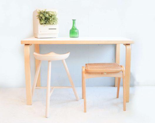 """素材の温もりとオーガニックでシンプルなデザインの名作テーブルでこちらのテーブルをデザインしたAlvar Aalto(アルヴァ・アアルト)は、家具デザインだけではなく数々の名建築を生み出し、北欧モダンデザインの思想を構築した一人でもあります。アルテック定番のロングセラースツール60と「アアルトレッグ」と呼ばれる特徴的な脚部は、ムクのバーチ材を曲げるための工夫とシンプルな接合、 余計な金具を使わない特殊な加工技術で成形されており、特許も取られています。バーチは日本語で樺(カバ)フィンランド産の樺材に代表されるように北欧家具で使用されることが多い木材で、近年は温暖化の影響で良質のバーチが採れにくくなってしまっている木材でもあります。温かくすっきりとしたフォルムとサイズ感は、デスクやダイニングとしても利用できるかと思います。特許を取ったL字型の脚は、ムクのバーチ材を曲げるための工夫と、座面とのシンプルな接合で、永年のロングセラーとなっています。近年温暖化の影響で、良質のバーチが採れにくく、環境保護の為、裏面などの見えにくい部分には節や傷のような箇所がある場合がございます。ご使用頂く際には問題ございませんが予めご了承ください。バーチは日本語で樺(カバ)。フィンランド産の樺材に代表されるように北欧家具で使用されることが多い木材です。見た目と性質がサクラと似ているため、日本語ではカバザクラやサクラとも呼ばれ、サクラの代用として使われることもあります。材質は硬く、均等で緻密な木肌を持ち、反りなどの狂いが少ないのが特徴です。水に強く、粘りや強度もあるため床材や家具材として使用されることが多いです。「アアルトレッグ」と呼ばれる特徴的な脚部アアルトがデザインした家具の特徴は、木を曲げる独特な手法にあります。通称「アアルトレッグ」と呼ばれる柔らかな曲線を描く脚部は、余計な金具を使わない特殊な加工技術で成形しています。このL字型の脚部を天板にネジ止めしただけのシンプル構造で、素材感を活かした温かく柔らかなフォムを実現しています。素材の温もりを感じるオーガニックなデザインテーブルの名作です。W1200×D600×H720mmAlvar Aalto (Alvar Aalto) who designed this table with a warmth of materials and a masterpiece of an organic and simple design produced not only furniture design but also numerous name constructions, even one who built the thought of Northern European design Yes. The characteristic legs called Altech's classic long-selling stool 60 and """"AALT LEGG"""" are the ingenuity and simple joining for bending Muku's birch material, It is molded by special processing technology that does not use extra metal fittings, and patent is also taken. Birch is Japanese wild birch (Hippo) Wood used in Scandinavian furniture as typified by Finland birch wood, and in recent years it has become difficult to obtain high quality birch due to global warming effect It is also wood. I think whether you can use it as a desk or dining, feeling warm and refreshing form and size. The patented L-shaped leg is a long seller of many years, with a device for bending the bamboo material of Muku and a simple joining with the seat. In recent years due to global warming, good quality birch is difficult to collect,"""