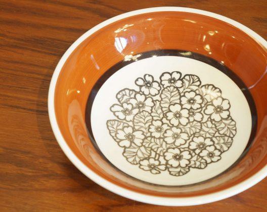 """Gefle/ゲフレ社、""""Agneta/アグネッタ""""シリーズのスープボウル。 ゲフレは1910年にスウェーデンで創業した陶磁器メーカーです。 同じスウェーデンのグスタフスベリなどと比べると少しマイナーですが、 こちらのアグネッタシリーズやブルーのグラデーションが美しいコスモスシリーズなどが 人気のスウェーデンを代表する窯のひとつです。 1935年に同じくスウェーデンのウプサラエクビー社に買収されましたが、 1979年までゲフレのブランド名で陶磁器を作り続けました。 アグネッタシリーズはゲフレを代表する人気デザイナー、ヘルメル・リングストロームの デザインと言われていますが、実際には詳細不明です。 ヘルメル・リングストロームの他のシリーズ同様、絵柄をスタンプしたような作風が アグネッタシリーズにもみられるので、おそらく彼のデザインかと…。 こっくりとした深みのあるオレンジブラウンのカラーとボウルの底に 敷き詰められたたくさんのお花が目を引く、とっても可愛らしいデザインです。 花柄はおそらくスタンプでプリントされており、色の濃淡やちょっとしたかすれなど、 手書きの絵柄とはまた違った雰囲気が楽しめます。 落ち着いた色合いの大人っぽいデザインは、きっとどんなシチュエーションにも使いやすいはず。 可愛らしくてどこか懐かしいような、北欧らしいデザインの食器はいかがでしょうか♪ ~【東京都杉並区阿佐ヶ谷北アンティークショップ 古一/ZACK高円寺店】 古一/ふるいちでは出張無料買取も行っております。杉並区周辺はもちろん、世田谷区・目黒区・武蔵野市・新宿区等の東京近郊のお見積もりも!ビンテージ家具・インテリア雑貨・ランプ・USED品・ リサイクルなら古一/フルイチへ~"""