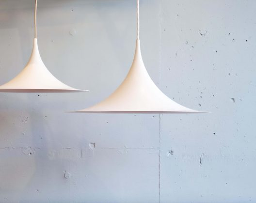 デンマーク出身のClaus BonderupとTorsten Thorupによって1967年に 発表されたペンダントライト『SEMI』。 当時はまだ二人ともデンマーク王立アカデミーで建築を学ぶ学生でした。 美しい曲線を描く幾何学的なシェードは一枚のアルミを絞り出して作り出されています。 四分の一の円弧を二つ背中合わせにつなげたという、シャープさと繊細さを兼ねそろえた 建築家の彼ららしいデザインです。 とてもシンプルなフォルムですが、他の照明とは一線を画すような独特な存在感を放ちます。 当初はデンマークを代表する照明メーカー『Fog&Morup』社から販売されていましたが、 当時のデンマークは企業の買収が盛んだったため、その後『Fog&Morup』社は何度も買収され、 『LYFA-Fog&Mørup』、『Lyskær-LYFA』、『LyskærBelysning』、 『Horn Belysning(Horn Lighting)』と名前が変わっていきます。 こうして会社が変わっても『SEMI』は作られ続けました。 現在は同じデンマークの家具メーカー『GUBI』が製造販売しています。 日本でも、ヤマギワがライセンスを取得し、製造販売をしていた時期もあるほど。 メーカーや国を越えて作られ続ける世界的ベストセラーであるということがうかがえます。 今回入荷したものは1991年に『LyskærBelysning』社を買収した 『Horn Belysning(Horn Lighting)』社製の『SEMI MINI』サイズと それより一回り小さいサイズの二種類。 一つずつ使ってももちろん良いのですが、大小の二つを並べて吊るすのがおすすめです。 二つ並ぶ姿はまるで『SEMI』の親子のようでとってもかわいいのです。 この二種類が同時に入荷することはかなり珍しいので、並べて使いたいという方は必見です。 発売から50年以上経った今もなお、デンマークデザインを代表するアイコンとして 愛され続けるペンダントライト『SEMI』。 シンプルだけど特徴的な北欧の灯りをぜひ味わってみてはいかがでしょうか♪ ~【東京都杉並区阿佐ヶ谷北アンティークショップ 古一/ZACK高円寺店】 古一/ふるいちでは出張無料買取も行っております。杉並区周辺はもちろん、世田谷区・目黒区・武蔵野市・新宿区等の東京近郊のお見積もりも!ビンテージ家具・インテリア雑貨・ランプ・USED品・ リサイクルなら古一/フルイチへ~