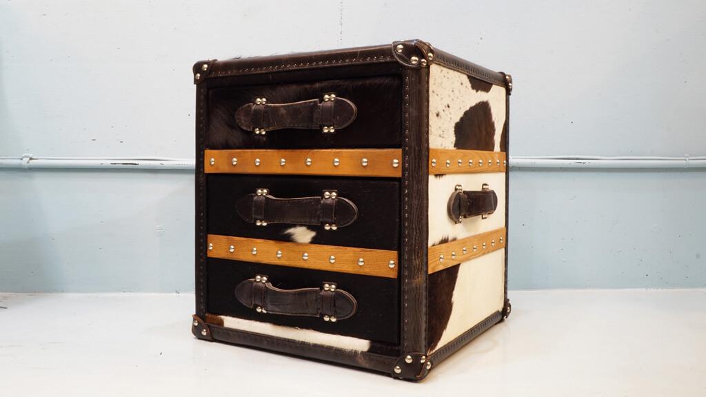 英国でアンティーク家具の販売とリノベーションから始めたHALO/ハロ。後にアンティーク家具のリプロダクトに着手。伝統的なデザインや製法にインスピレーションを得て、ユニークな発想から現代的で斬新なヴィンテージスタイルの家具を次々と発表しています。そんなHALO/ハロが、「旅」というコンセプトをもとに、ヴィンテージトランクからインスピレーションを得て生み出された、テーブルやチェストの人気シリーズである【STONYHURST/ストニーハースト】 。使われる数百の鋲はすべて機械ではなく手作業で打ち込むなど、膨大な時間をかけて製作されています。リビングや寝室などでサイドテーブルとしてお使いいただけるトランクをモチーフとした2段チェストです。見た目では3段に見えますが、中央は飾り取手になっている遊び心のあるデザインです。上段は浅め、下段は深さのある引出しになっています。こちらの品は、全面に牛柄の毛を用いたMOOモデル。黒と白の毛並みが高級感と重厚感を感じさせる一台で、内装もシックなブラック仕様。アンティークトランクをモチーフにした、モダンでモードテイスト溢れるアイテムに仕上げています。変わったチェストをお探しの方は是非♪ ~【東京都杉並区阿佐ヶ谷北アンティークショップ 古一/ZACK高円寺店】 古一では出張無料買取も行っております。杉並区周辺はもちろん、世田谷区・目黒区・武蔵野市・新宿区等の東京近郊のお見積もりも!ビンテージ家具・インテリア雑貨・ランプ・USED品・ リサイクルなら古一へ~