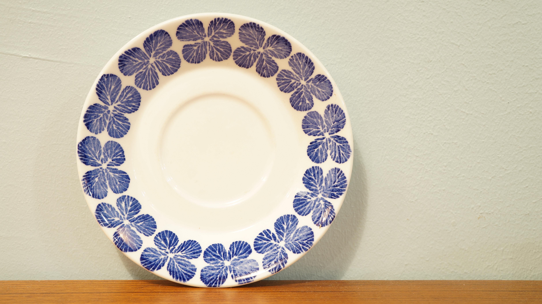 """スウェーデン、グスタフスベリ社の""""スティーナ""""シリーズのカップ&ソーサー。 デザイナーはグスタフスベリの全盛期を支えた、天才デザイナー、スティグ・リンドベリ。 日本では1959年に西武百貨店の包装紙のデザインを手がけたことで有名になりました。 """"スティーナ""""は白地に可愛らしいブルーの四葉のクローバーがプリントされたシリーズ。 とても優しい雰囲気が溢れるカップ&ソーサーです。 小ぶりなサイズなので、ちょっとだけお茶を飲みたいときにも。 貴重なヴィンテージ食器をぜひご自宅でもお楽しみください♪ ~【東京都杉並区阿佐ヶ谷北アンティークショップ 古一/ZACK高円寺店】 古一では出張無料買取も行っております。杉並区周辺はもちろん、世田谷区・目黒区・武蔵野市・新宿区等の東京近郊のお見積もりも!ビンテージ家具・インテリア雑貨・ランプ・USED品・ リサイクルなら古一へ~"""