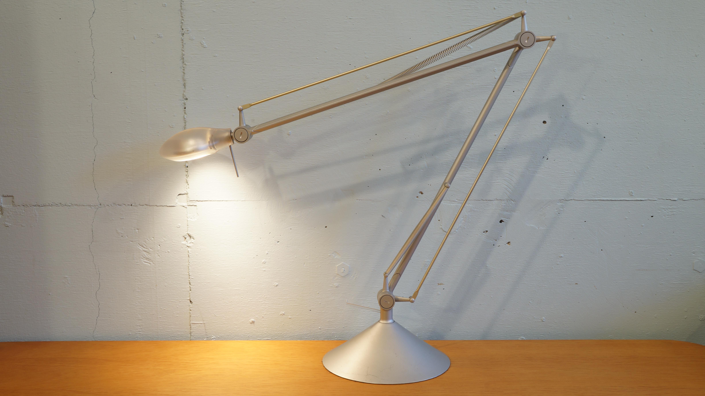 """建築・インテリア・家具・食器・出版物・インダストリアルデザイン等さまざまな分野のデザインを手がける、フランスを代表する世界的デザイナーフィリップ・スタルクがデザインした、""""アーキムーン テック""""デスクライト。スケルトンの丸いシェードとシンプルで直線的なアームが印象的です。アームはフレキシブルに動かせるので、自分の好きな高さに調節できます。デスクにはもちろん、ベッドサイドに置いて就寝前のリラックスタイムのお伴にお使いいただくのもいかがでしょうか。今では生産されていない商品ですので、お探しの方はこの機会にぜひ!~【東京都杉並区阿佐ヶ谷北アンティークショップ 古一/ZACK高円寺店】 古一/ふるいちでは出張無料買取も行っております。杉並区周辺はもちろん、世田谷区・目黒区・武蔵野市・新宿区等の東京近郊のお見積もりも!ビンテージ家具・インテリア雑貨・ランプ・USED品・ リサイクルなら古一/フルイチへ~"""