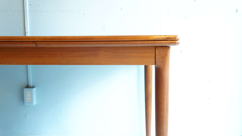 デンマーク製、ドローリーフタイプの伸長式ダイニングテーブル。美しい木目と滑らかな木肌のチーク材が使われています。ドローリーフとは、英国アンティークによく見られる両サイドの天板を引き出して伸長するタイプですのでメインの天板に線が入らず片方のみを伸ばしてご使用頂けます。脚はシンプルなデザインの中にも、付け根には北欧家具ならではの緩やかな丸みを帯びたアールが印象的です。幅も通常で約130cm御座いますので、二人並んだ状態でも窮屈に感じずお使い頂けます。何より最大幅約250cmですので、ご来客やパーティーなどに活躍してくれます。天板に目立つキズもなく、これからも末永くご使用いただけるお品物です。是非この機会にいかがでしょうか。〜【東京都杉並区阿佐ヶ谷北アンティークショップ 古一/ZACK高円寺店】 古一/ふるいちでは出張無料買取も行っております。杉並区周辺はもちろん、世田谷区・目黒区・武蔵野市・新宿区等の東京近郊のお見積もりも!ビンテージ家具・インテリア雑貨・ランプ・USED品・ リサイクルなら古一/フルイチへ