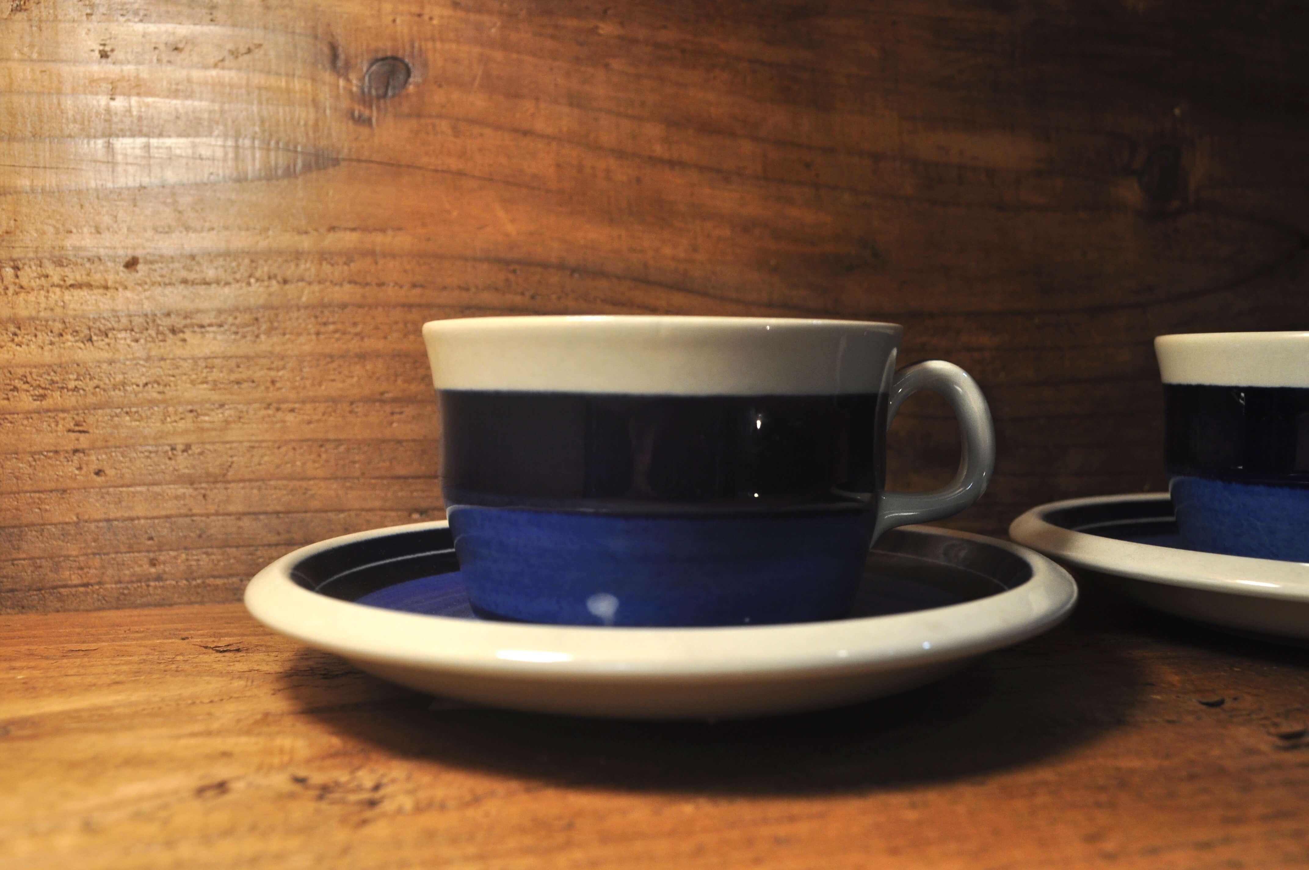 北欧スウェーデンのブランド「ロールストランド」、ミラマーレシリーズのコーヒーカップ&ソーサーです。デザイナーはマリアンヌ・ウエストマンで、同じフォルムのAnnika/アニカやElisabeth/エリザベスに比べて生産数が少なく、希少なシリーズです。「Mira Mare」とは、イタリア北東部、スロベニア国境に近い町・トリエステに建てられた、19世紀の城の名前。グレーがかった素地で城を、2色のブルーでアドリア海を表現していて、湾岸に建てられて海に浮かぶように見える城を抽象化したデザイン。 濃いブルーは深みが、薄いブルーは鮮やかさがあって、明るく開放的なイタリアの海に北欧の人々があこがれる気持ちを表現したかのようです。