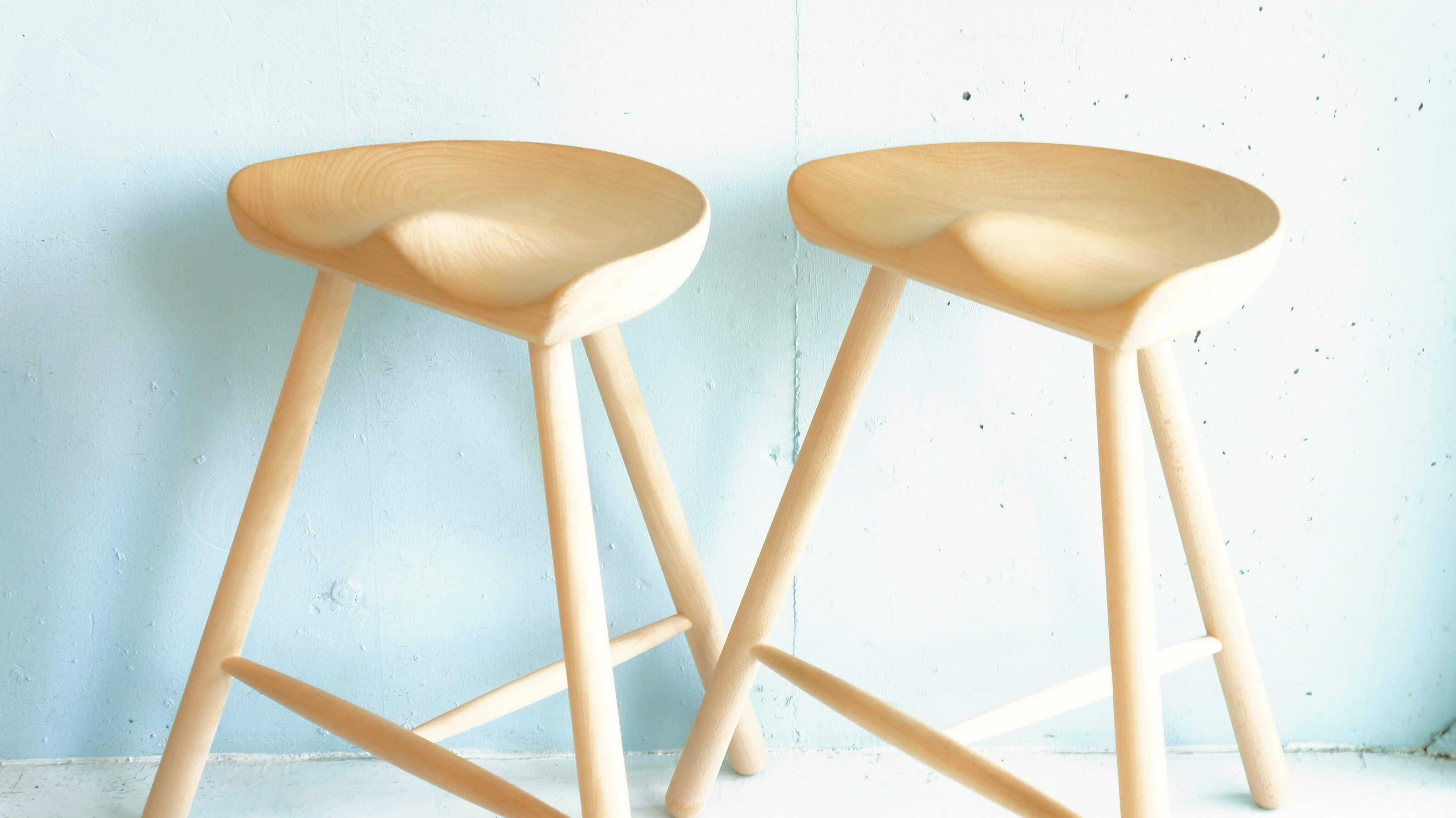 シューメーカーチェアは、15世紀のデンマークの農民たちが牛の乳搾りの時に使っていた3本脚のスツールがはじまりと言われています。当時のデンマークは石畳の凸凹した床が多く、4本脚よりも3本脚の方が安定して座れたことから、3本脚のスツールや椅子が重宝されました。その後、デンマークでは木靴の生産が盛んになり、靴職人が3本脚のスツールを使っていたところ、摩擦で座面がおしりの形に自然と削れ、さらに座り心地を良くするためにそれぞれのおしりの形にフィットするよう削っていくようになり、現在の形に近づきました。それがこのいすが「シューメーカーチェア」と言われる所以です。それにインスピレーションを受け、現在のワーナー社のオーナー、ラース・ワーナーの父親が1970年代初めにシューメーカーチェアの製作を始めました。座面を大まかに機械で削り出したあと、職人がひとつひとつ手作業で仕上げています。材質は無垢のブナ材。デンマークのブナ材は材木として切り倒すことができるように成長するまで、80~120年かかると言われており、これは材木がとても硬質であることを意味しています。さらに、3本脚の間にT字に貫(ぬき)が入ることにより頑丈な作りになっており、また、使用するときの足置きにもなります。ワーナーのシューメーカーチェアにはいくつかサイズがありますが、こちらは高さ59cmのモデル。カウンターに合わせると丁度良いサイズです。デンマークの伝統が息づく、シンプルで洗練されたデザイン性と機能性に優れたいす。使うほどに体に馴染んでいき、一生もののスツールになることでしょう。こだわりのスツールや椅子をお探しの方はぜひいかがでしょうか♪~【東京都杉並区阿佐ヶ谷北アンティークショップ 古一/ZACK高円寺店】 古一/ふるいちでは出張無料買取も行っております。杉並区周辺はもちろん、世田谷区・目黒区・武蔵野市・新宿区等の東京近郊のお見積もりも!ビンテージ家具・インテリア雑貨・ランプ・USED品・ リサイクルなら古一/フルイチへ~