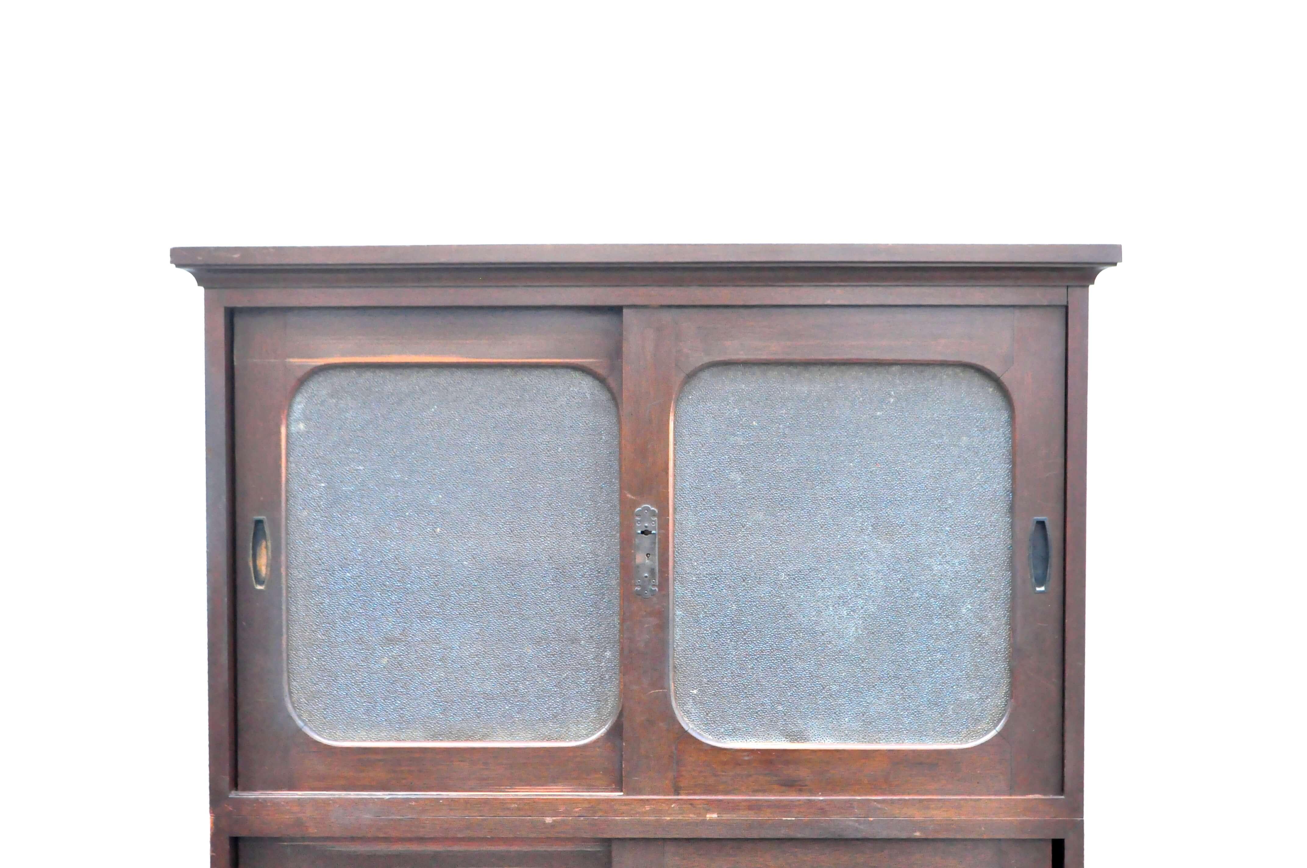 日本のアンティークキャビネット。回顧的なデザインや、長い年月を経て生まれた木の深みを味わえるお品物。古いガラス独特の模様が時代を感じさせてくれます。こちらのガラスの模様は、ダイヤガラスと呼ばれ1935年から日本国内で製造された結霜ガラスと同様に日本の代表的なレトロガラスの一種です。このように、表面の無数の切り込み模様が特徴で、光にあたるとダイヤのように輝きを放ちます。ガラスの特性で物のシルエットがぼやけるので、色があるものを収納するとの彩りも美しいです。食器の収納はもちろん、小ぶりなサイズ感ですのでお好きなインテリア雑貨などを収納して飾り棚としてお使い頂けるかと思います。