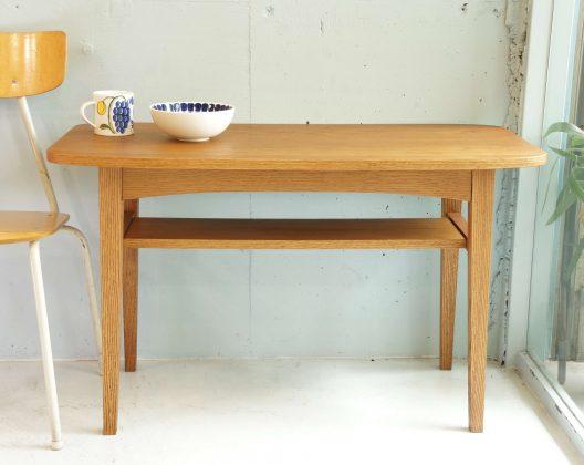 """ウニコの人気シリーズ""""KURT""""のカフェテーブル。オーク材の木目が美しく、温かみのある北欧ヴィンテージスタイル。はっきりとでた木肌の質感は、ナチュラルやアメリカンなインテリアテイストにも馴染みやすいデザインです。床に座った状態での使用には少々高めで、椅子や、ソファに座ったまま、お食事やパソコン作業もしやすい高さに設計されております。リビングにてセンターテーブルとしてとしての使用や、ラウンジテーブルなどにも扱いやすく、自宅でカフェスタイルを楽しめるデザインです。中々北欧ビンテージや現行の家具にも見ないコンパクトで、スモールスペースにぴったりなサイズ感♪天板下は、雑誌や小物をさっとしまえる便利な棚が付いています♪参考上代価格39744円~unico,ウニコ,KURT,クルト ,カフェテーブル,テーブル,リビングテーブル,ラウンジテーブル,サイドテーブル,ローテーブル,ラウンドテーブル,センターテーブル,Cafe,table ,机,US,VINTAGE,TEAK,WOOD,LOW,TABLE,ビンテージ,チーク天板,ローテーブル,コーヒーテーブル,センターテーブル,US家具,ミッドセンチュリー,【東京都杉並区阿佐ヶ谷北アンティークショップ 古一/ZACK高円寺店】 古一/ふるいちでは出張無料買取も行っております。杉並区周辺はもちろん、世田谷区・目黒区・武蔵野市・新宿区等の東京近郊のお見積もりも!ビンテージ家具・インテリア雑貨・ランプ・USED品・ リサイクルなら古一/フルイチへ~"""