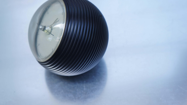 地球をイメージした球体の置時計  五十嵐威暢/earth clock アースクロック1987年に五十嵐威暢氏がOUN(アウン株式会社)のためにデザインしたearth clock。ボディーはモダンな黒いカラーリング、静かに回転する地平線のような秒針が印象的な置時計です。こちらの時計をデザインすることになった当時、球体の時計がつくられていないことに気付き球体は地球のイメージとつながり、地球の70%をしめる大海原を時計ボディに施した波形の溝で表現しました。透明なドームで覆われた文字盤部分は、残る30%の大地を表しています。大地の上では、秒針が秒針を追いかけ流れるように動き、終わりのない時間を感じることができますearth clockの本体は砂型鋳物の技術を用いて製作。波形の細かな表面形状は 補修を加えることができないため、鋳物自体の完成度の高さが求められます。その後の旋盤加工は、形状が絶妙であるため切削可能な部分が極めて少なく、精緻な準備と加工を必要とします。熟練職人の経験と技によりこの複雑な形状を表現しています。復刻品も販売されておりますが、こちらは1987年に販売されたオリジナル商品です。中古市場でも数の少ないお品物です。お探しだった方は是非この機会にいかがでしょうか。≪ Takenobu Igarashi / 五十嵐 威暢 ≫彫刻家、デザイナー。アクソノメトリック図法によるニューヨーク近代美術館のカレンダー、立体アルファベット、サントリーホール・カルピスのVIデザイン、OUNやYMDのプロダクトなど、グラフィック・プロダクトデザイナーとして活動し、世界的な評価を受けている。1994年、彫刻家に転身。木、石、金属、テラコッタ、ステンドグラスなど、様々な素材でパブリックアートとしての作品を数多く制作している。多摩美術大学名誉教授。