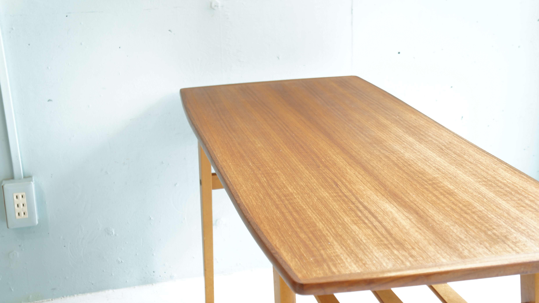 チーク材を天板に使用した、マガジンラック付きビンテージ コーヒー/センターテーブルが入荷致しました。日本の古い家具にも馴染みのあるマガジンラック付きの脚に木目の綺麗なチークが相性よく、やわらかな印象を与えてくれます。アメリカのビンテージ家具ですが、北欧インテリアや和テイスト、ナチュラルスタイルなど様々なインテリアスタイルに合うローテーブルです。通常のローテーブルよりも、高さがございますので少し座面の高いソファにも、違和感なくお使い頂けます。アラビアなどの北欧食器やファイヤーキングなどのUSビンテージ系の食器と合わせたくなるこちらのローテーブル。是非この機会にいかがでしょうか。~【東京都杉並区阿佐ヶ谷北アンティークショップ 古一/ZACK高円寺店】 古一/ふるいちでは出張無料買取も行っております。杉並区周辺はもちろん、世田谷区・目黒区・武蔵野市・新宿区等の東京近郊のお見積もりも!ビンテージ家具・インテリア雑貨・ランプ・USED品・ リサイクルなら古一/フルイチへ~