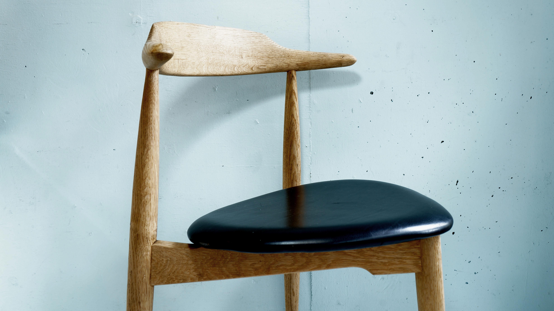 デンマークの巨匠、ハンス・J・ウェグナーが1952年に発表した三本脚の椅子、通称ハートチェア。 フリッツ・ハンセン社から約12年間、スタンダード製品として製造されていました。 特徴的な三角形の座面はハート形に見えることから、ハートチェアと呼ばれるようになりました。 当時のデンマークは凸凹の石畳の床が多く、四本脚よりもより安定した三本脚の椅子が多く作られました。 このハートチェアは三本脚のチェアの原点とも言われています。 また、ハンス・J・ウェグナーデザインの円形のテーブル、通称ハートテーブルに 6脚収納できるようにデザインされています。 同じくハートチェアと呼ばれているFH-4103とは少しデザインが異なり、 背もたれ部分が少し横に長くなっており、両端は短い肘掛けのようになっています。 また、FH-4103の座面は突板ですが、こちらのFH-4104は座面にレザーが張られています。 オーク材のあたたかみのある雰囲気にシャープですっきりとした印象のブラックのレザーが 組み合わさることで、ナチュラルスタイルやモダンスタイルにもよく合います。 さらにそのシンプルでミニマルなデザインが、洗練された空間を演出してくれます。 ハートチェアはヴィンテージ品でしか出会うことができない、とても希少なチェアです。 シンプルで美しく無駄のないウェグナーならではのデザインのチェアをぜひ。 ~【東京都杉並区阿佐ヶ谷北アンティークショップ 古一/ZACK高円寺店】 古一/ふるいちでは出張無料買取も行っております。杉並区周辺はもちろん、世田谷区・目黒区・武蔵野市・新宿区等の東京近郊のお見積もりも!ビンテージ家具・インテリア雑貨・ランプ・USED品・ リサイクルなら古一/フルイチへ~