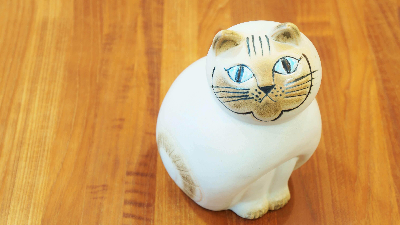 世界中で愛される、北欧を代表する陶芸家リサ・ラーソン。 1954年にスウェーデンGUSTAVSBERG社に入社し、1979年に退社するまでの約20年間の間に数多くの作品を発表しました。 80歳を超える現在でも精力的に作品を製作し、活動しています。 こちらは、1965年にデザインされたSTORA ZOOシリーズのMia Cat/ミアキャットの復刻版。 まんまるのフォルムと見上げてこちらをじっと見つめる表情がたまらなくかわいいネコです。 カラーとサイズのバリエーションがあるシリーズですが、こちらは白い体に茶色の顔のカラーリング、 そして存在感のある高さ約19cmのサイズです。 思わず抱きしめたくなるサイズ感…! リサ・ラーソンデザインのフィギュリンは、職人さんが一点一点、手作業で仕上げているため、 焼き色具合や細かな表情、刻印の入れ方が全て異なっているため、二つと同じものがないというのも 作品のひとつの味となり、特徴となっています。 ネコ好きというリサ・ラーソンらしい、ネコのかわいい魅力が詰まったフィギュリン。 目に入るたびにほっこりとした気分になり、その場に癒しの雰囲気を与えてくれること間違いなし! ぜひ、お気に入りの場所に置いてあげてください♪ ~【東京都杉並区阿佐ヶ谷北アンティークショップ 古一/ZACK高円寺店】 古一/ふるいちでは出張無料買取も行っております。杉並区周辺はもちろん、世田谷区・目黒区・武蔵野市・新宿区等の東京近郊のお見積もりも!ビンテージ家具・インテリア雑貨・ランプ・USED品・ リサイクルなら古一/フルイチへ~