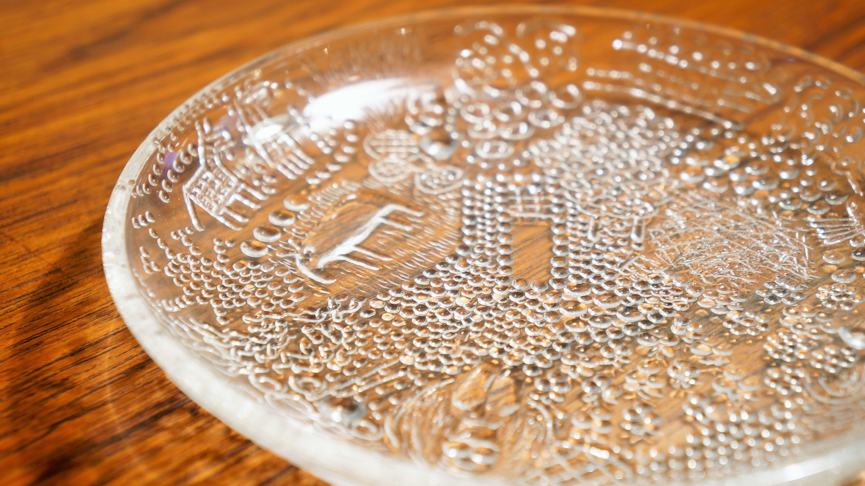 """1793年に設立されたフィンランドで最も古いガラス工場、Nuutajarvi/ヌータヤルヴィ。 1881年に設立されたイッタラよりも100年近くも古いという歴史のある工場です。 現在では、イッタラの傘下として操業しています。 こちらは""""ファウナ""""シリーズの15cmのプレート。 """"Fauna/ファウナ""""とは動物相という意味。 その名の通り、ガラスの凹凸で表現されたお花や植物の模様の中に 様々な動物を何匹も見つけることができます。 デザイナーはフィンランド出身のオイバ・トイッカ。 オイバ・トイッカは""""カステヘルミ""""シリーズや""""バード""""シリーズで知られる、ガラスアーティストです。 1962年にヌータヤルヴィに入社し、同じフィンランド出身のデザイナー、カイ・フランクと一緒に 様々な実験的試みを行い、また、ブロウ職人とともにたくさんの革新的なブロウ技術を編み出しました。 可愛らしい動物柄はお子さま用にぴったりですが、もちろん大人が使ってもいいんです。 フルーツやプリン、アイスなどを盛り付けたらとっても爽やか。 食べ終わったら動物たちがひょっこり顔を出し、なんだかほっこり。 そんな癒し系の食器はいかがでしょうか♪ ~【東京都杉並区阿佐ヶ谷北アンティークショップ 古一/ZACK高円寺店】 古一/ふるいちでは出張無料買取も行っております。杉並区周辺はもちろん、世田谷区・目黒区・武蔵野市・新宿区等の東京近郊のお見積もりも!ビンテージ家具・インテリア雑貨・ランプ・USED品・ リサイクルなら古一/フルイチへ~"""