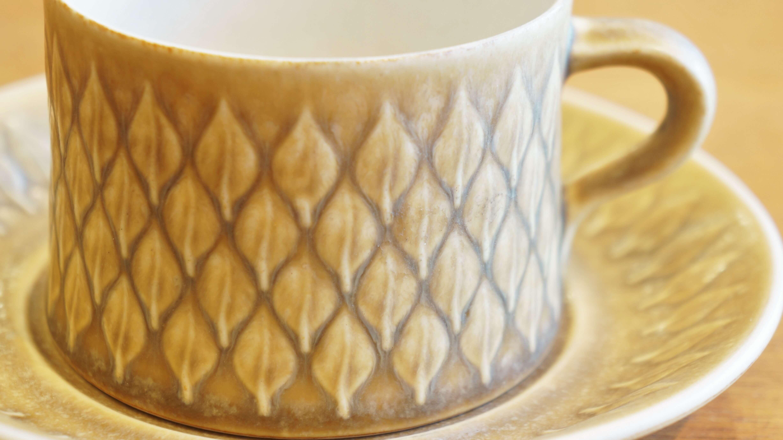 """DANSKの創業者としても知られる、デンマーク出身のデザイナー、 イェンス・H・クイストゴーが手掛けた、クロニーデン社製 """"レリーフ""""のティーカップ&ソーサー。 サンドイエローのカラーに木の葉のモチーフを凹凸で表した、 北欧らしいあたたかみのあるデザインです。 レリーフは少しザラっとした独特なマットな質感が特徴です。 和食器から影響を受けたというクイストゴーの作品はどれも 日本の食卓に自然と馴染んでくれるようなものばかり。 50年代デンマークの窯業は、企業の合併や買収が盛んであったため、 レリーフをはじめとするクイストゴーの作品は3つの異なる会社の刻印があります。 レリーフシリーズはKronjyden社、Nissen社、Bing & Grondahl社と会社が変わっても 生産され続けた人気の高いシリーズです。 ほっこりさせてくれるようなやさしい雰囲気の""""レリーフ""""。 お茶の時間をより一層リラックスさせてくれるようなカップ&ソーサーはいかがでしょうか♪ ~【東京都杉並区阿佐ヶ谷北アンティークショップ 古一/ZACK高円寺店】 古一/ふるいちでは出張無料買取も行っております。杉並区周辺はもちろん、世田谷区・目黒区・武蔵野市・新宿区等の東京近郊のお見積もりも!ビンテージ家具・インテリア雑貨・ランプ・USED品・ リサイクルなら古一/フルイチへ~"""
