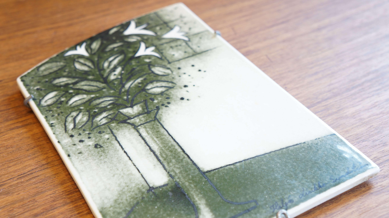 可愛らしいウサギが登場する絵本「地平線のかなたまで」の著者であり、 陶芸作家や画家、絵本作家として有名なフィンランド生まれのデザイナー、 ヘルヤ・リウッコ・スンドストロムのウォールプレート。 アラビアのアート部門であるアートデパートメントに 1962年から1967年まで在籍していました。 淡い緑と白の2色というシンプルなカラーリングで ユリの花が生けられた花瓶が部屋の隅にそっと置いてあるという風景が 描かれています。 このウォールプレートは12.5cm×19cmという小さなサイズの中にも ほのぼのとした彼女らしい、独特な世界観が存分に表現されています。 すべてハンドペイントされたウォールプレートはなかなか流通しない、 レアなアイテムです。 ぜひ、ヘルヤ・リウッコ・スンドストロムの世界をお楽しみください♪ ~【東京都杉並区阿佐ヶ谷北アンティークショップ 古一/ZACK高円寺店】 古一/ふるいちでは出張無料買取も行っております。杉並区周辺はもちろん、世田谷区・目黒区・武蔵野市・新宿区等の東京近郊のお見積もりも!ビンテージ家具・インテリア雑貨・ランプ・USED品・ リサイクルなら古一/フルイチへ~