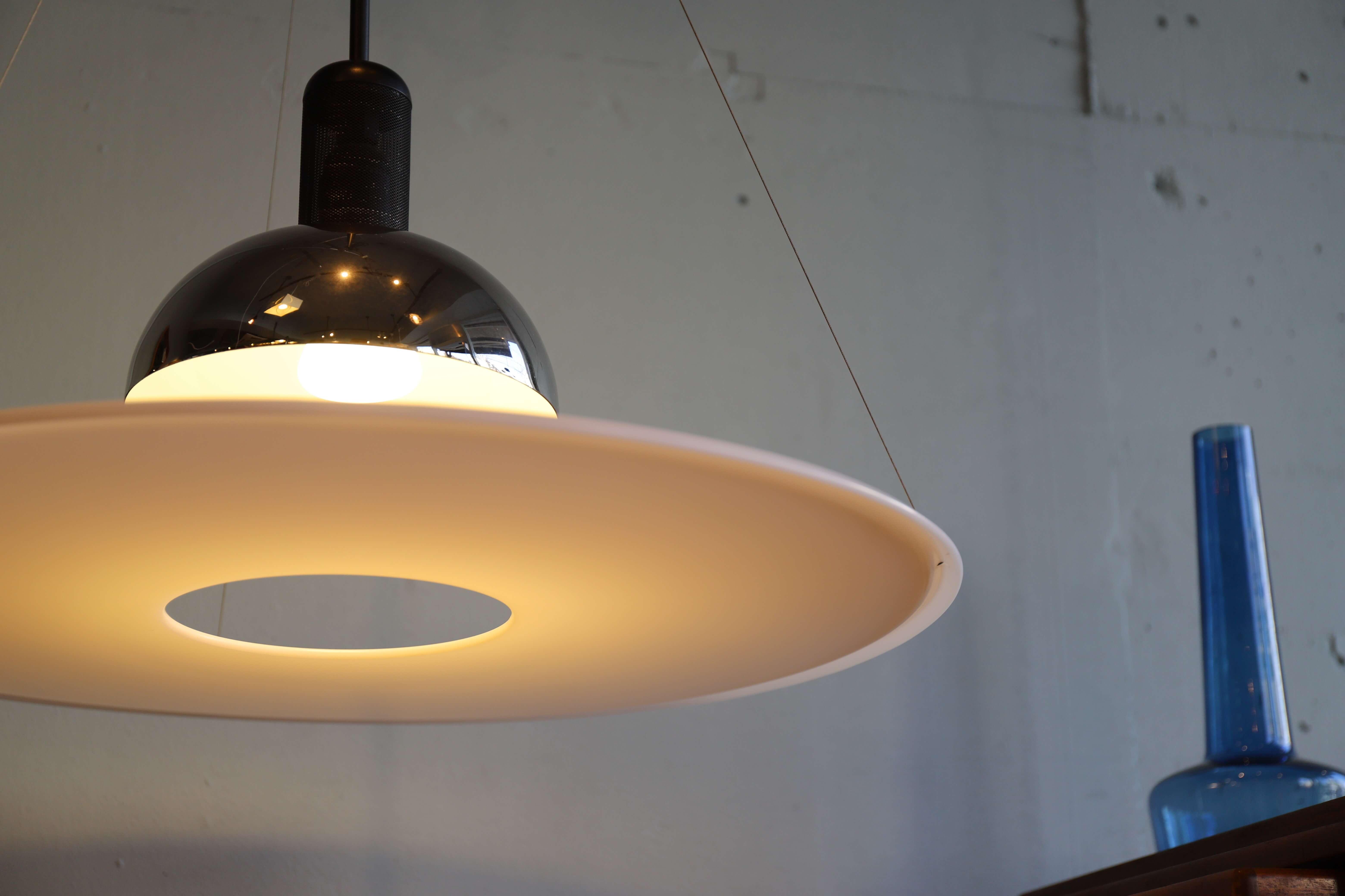 """1962年創立のモダン照明のトップブランド、『FLOS』。 そのFLOSの立ち上げで異才を大いに発揮した、イタリア出身のデザイナー、 アッキーレ・カスティリオーニが手掛けたペンダントライト、「FRISBI/フリスビー」。 """"フリスビー""""という名前の通り、円盤型のシェードが宙に浮かんでいるようなユニークなデザイン。 あかりを灯すと、中心の穴から真下に向かって光が射し、その周りで反射した光を 円盤型のシェードが柔らかく拡散してくれます。 お部屋が要所要所で必要とする光の条件を的確に満たし、 直接的な光と間接的な光の両方を上手く利用できるようにデザインされた、ダイニングに ぴったりなペンダントライトです。 また、真下以外は光源が直接目に入らないようになっているので、眩しさを防ぎ、 やさしい光で照らしてくれます。 私たちが日々の生活の中で""""明かり""""に求めるものを、強弱の光を巧みに操り、 ひとつのツールで見事に作り上げた、アッキーレ・カスティリオーニ。 フリスビーは『デザイナーの個性を強く主張するよりも、使い手の視点で物作りをする』という、 彼の思想が具現化されたデザインのひとつです。 淡い光と独特な存在感を放つ、「FRISBI/フリスビー」。 これもまたデザイン性と実用性を兼ねそろえた、実に優れたプロダクト。 変わったデザインが好きな方にはぜひフリスビーの光を体験していただきたいです。 ~【東京都杉並区阿佐ヶ谷北アンティークショップ 古一/ZACK高円寺店】 古一/ふるいちでは出張無料買取も行っております。杉並区周辺はもちろん、世田谷区・目黒区・武蔵野市・新宿区等の東京近郊のお見積もりも!ビンテージ家具・インテリア雑貨・ランプ・USED品・ リサイクルなら古一/フルイチへ~"""