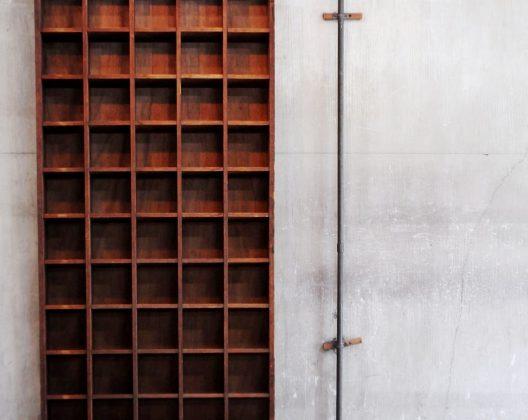 薄くて大きな体とたくさんの升目… こちらは昔の郵便局で使われていた、手紙を仕分けるための棚なんです。 斜めになっている棚板は手紙を取りやすくするためと、 棚から落ちにくくするため。 なるほど、郵便屋さんが手紙を仕分けしやすいような、 ちょっとした工夫がなされているという訳です。 もちろんお家でこれだけの量の手紙を仕分けることなどありませんから、 お家ではディスプレイシェルフとして、お気に入りの雑貨などを 並べてみてはいかがでしょうか。 CDもぴったり収まるサイズです。 これだけあれば相当な枚数を収納できますね。 また、お店の什器としてもおすすめです。 使い込まれた木の風合いはとってもいい雰囲気を演出してくれます。 これだけ大きいとかなりインパクトもあります。 アイデア次第でいろいろな使い方ができます。 ほとんど手紙を送ることがなくなってしまった現代の私たちですが、 これで当時の郵便屋さんが手紙を仕分けていたのかと思うと なんだかノスタルジーを感じずにはいられません。 時と共に増した味わいを、こうして違う使い方でも味わえるの、いいものです。 ※大型、薄型であるため、倒れやすくなっています。 壁に取り付けるか、他の物でこの棚を支えるように設置してください。 ~【東京都杉並区阿佐ヶ谷北アンティークショップ 古一】 古一/ふるいちでは出張無料買取も行っております。杉並区周辺はもちろん、世田谷区・目黒区・武蔵野市・新宿区等の東京近郊のお見積もりも!ビンテージ家具・インテリア雑貨・ランプ・USED品・ リサイクルなら古一/フルイチへ~