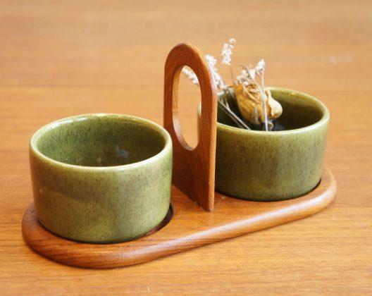 北欧、スウェーデンの老舗陶器メーカー「Jie Gantofta/ジィ ガントフタ」の かわいらしいスパイスボウルセット。 茶色い斑点が混ざった絶妙な色合いのグリーンの小さなボウルがふたつ、 チーク材を使ったトレーの上に乗っています。 トレーにハンドルがついているのも使いやすいです。 片方にはくし形に切ったレモンを、もう片方にはおかわり用のパクチーを。 なんて、タイ料理のトッピング用に使ってみたり。 こんなふうに調味料入れとしてはもちろんですが、 アクセサリーや鍵を入れて、小物入れとしても使えます。 艶のあるボウルと、木目の美しいチーク材のトレイの コントラストが楽しめるスパイスボウルセットです。 北欧らしいあたたかみのあるカラーと質感の雑貨はいかがですか? ~【東京都杉並区阿佐ヶ谷北アンティークショップ 古一】 古一/ふるいちでは出張無料買取も行っております。杉並区周辺はもちろん、世田谷区・目黒区・武蔵野市・新宿区等の東京近郊のお見積もりも!ビンテージ家具・インテリア雑貨・ランプ・USED品・ リサイクルなら古一/フルイチへ~