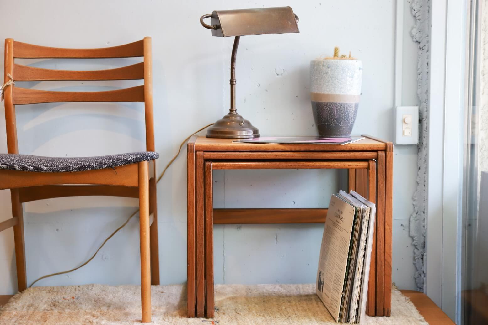 """1953年、イギリスの家具メーカーE.Gomme社が発表した、 北欧スタイルの家具ブランド『G-PLAN/ジープラン』。 E.Gomme社の創業者の孫であるドナルド・ゴムの『シンプルでモダンな家具を 作りたい』という発案から生まれました。 こちらは1960年代後半に作られた、ネストテーブル。 チーク材を使ったシンプルな北欧デザインにミッドセンチュリーの雰囲気を掛け合わせたような デザインが多くみられるG-PLANですが、このネストテーブルはG-PLANではちょっと珍しいくらい シンプルなデザインです。 一切の無駄を省いた、とことんシンプルなフォルムなので、 3つのテーブルをまとめると、スッキリ、きれいに、ピタッと、真四角に収まります。 大中小のサイズの差が少ないネストテーブルランキングがあるとすれば、 かなり上位を狙えるのでは?というくらい、シンプルなデザインだからこそ生まれるサイズ感です。 これまでこのネストテーブルのシンプルさを売りにお話してきましたが、 他にも見逃せないポイントがあります。 まずは、チーク材の杢目を合わせた寄木細工のような天板。 一枚の板でできた天板もいいけれど、たまにはこんな""""デザインされた天板""""も 味があっていいです。 そして最大のポイントは『組み木』になっている脚の接合部分。 8つの角にちょっとした組み木のアクセントを、なんて、 一見シンプルのようで、細かなところでさりげなくこだわりを見せる。 実に憎い演出です。 ただシンプルなだけでは物足りない、という方にオススメしたいネストテーブル。 お探しの方、ぜひいかがでしょうか♪ ~【東京都杉並区阿佐ヶ谷北アンティークショップ 古一】 古一/ふるいちでは出張無料買取も行っております。杉並区周辺はもちろん、世田谷区・目黒区・武蔵野市・新宿区等の東京近郊のお見積もりも!ビンテージ家具・インテリア雑貨・ランプ・USED品・ リサイクルなら古一/フルイチへ~"""