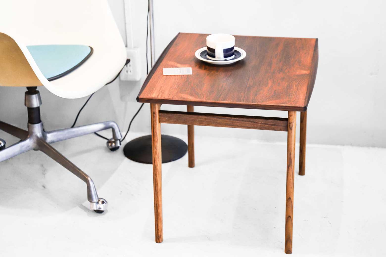ローズウッドの特徴である美しい木目と心地よい肌触りが存分に味わえるサイドテーブル。 天板両サイドのエッジ部分に色味の濃いローズウッドを組み合わせて作りだされた、緩やかで丸みのある反り返りが優しい印象を与えてくれます。 シンプルなだけでなく、ちょっとしたアクセントが効いた、細部までこだわりが感じられるテーブルです。 経年や使用による細かなキズや擦れがございますが、比較的状態は良好です。 ローズウッドらしい上品な艶となめらかな質感を永くお楽しみいただくために、定期的にオイルを塗ってメンテナンスしていただくことをおすすめいたします。 天板に目を落とす度に思わずうっとりしてしまうほどに美しい木目と、濃淡のあるローズウッドを組み合わせた色合いのコントラストが印象的なテーブルです。 ソファやベッドの隣で使えるコンパクトなサイズ感もまた魅力です。 ~【東京都杉並区阿佐ヶ谷北アンティークショップ 古一】 古一/ふるいちでは出張無料買取も行っております。杉並区周辺はもちろん、世田谷区・目黒区・武蔵野市・新宿区等の東京近郊のお見積もりも!ビンテージ家具・インテリア雑貨・ランプ・USED品・ リサイクルなら古一/フルイチへ~
