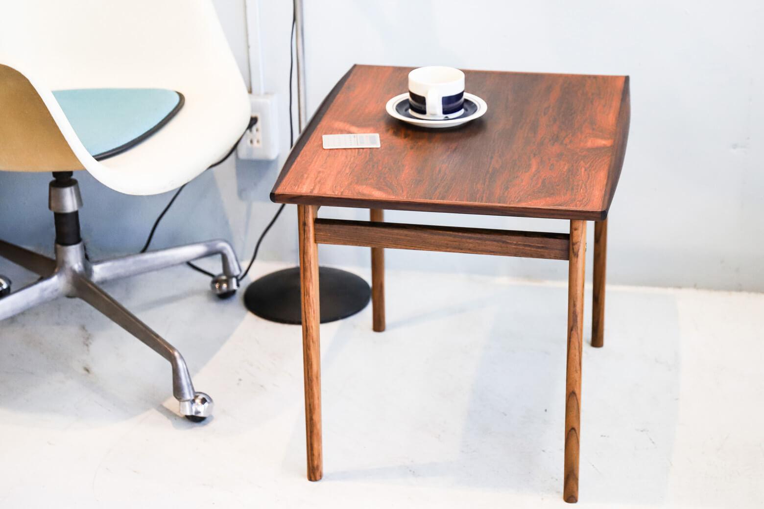 ローズウッドの特徴である美しい木目と心地よい肌触りが存分に味わえるサイドテーブル。 天板両サイドのエッジ部分に色味の濃いローズウッドを組み合わせて作りだされた、緩やかで丸みのある反り返りが優しい印象を与えてくれます。 シンプルなだけでなく、ちょっとしたアクセントが効いた、細部までこだわりが感じられるテーブルです。経年や使用による細かなキズや擦れがございますが、比較的状態は良好です。ローズウッドらしい上品な艶となめらかな質感を永くお楽しみいただくために、定期的にオイルを塗ってメンテナンスしていただくことをおすすめいたします。 天板に目を落とす度に思わずうっとりしてしまうほどに美しい木目と、濃淡のあるローズウッドを組み合わせた色合いのコントラストが印象的なテーブルです。ソファやベッドの隣で使えるコンパクトなサイズ感もまた魅力です。