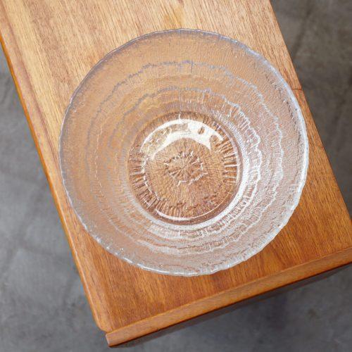 """フィンランドの厳しい自然モチーフにガラスを用いて表現した作品などを数多く残した、 フィンランドを代表するデザイナー、彫刻家のタピオ・ウィルカラ。 こちらは""""Solaris/ソラリス""""と名前がついたシリーズのサービングボウルです。 1974年に発表されて以来、1995年まで約20年間イッタラから販売されていました。 ソラリスとはラテン語で太陽という意味を持ちます。 ボウルの中心から放射状に線が広がっており、まさに太陽光が放たれているようなデザイン。 暑く眩しいはずの太陽の光を真逆の冷たい氷のような透明なガラスで、力強くかつクールに表現しています。 細かなキズやスレはございますが、ヒビや欠けなど大きなダメージはございません。 ソラリスシリーズは現在、廃盤になってしまっています。 今出会えるのはヴィンテージ物のみで、このサイズのボウルもなかなか希少なんです。 北欧フィンランドから生まれた、厳かな自然を体現したようなガラスのデザインをぜひ味わってください。 ~【東京都杉並区阿佐ヶ谷北アンティークショップ 古一】 古一/ふるいちでは出張無料買取も行っております。杉並区周辺はもちろん、世田谷区・目黒区・武蔵野市・新宿区等の東京近郊のお見積もりも!ビンテージ家具・インテリア雑貨・ランプ・USED品・ リサイクルなら古一/フルイチへ~"""