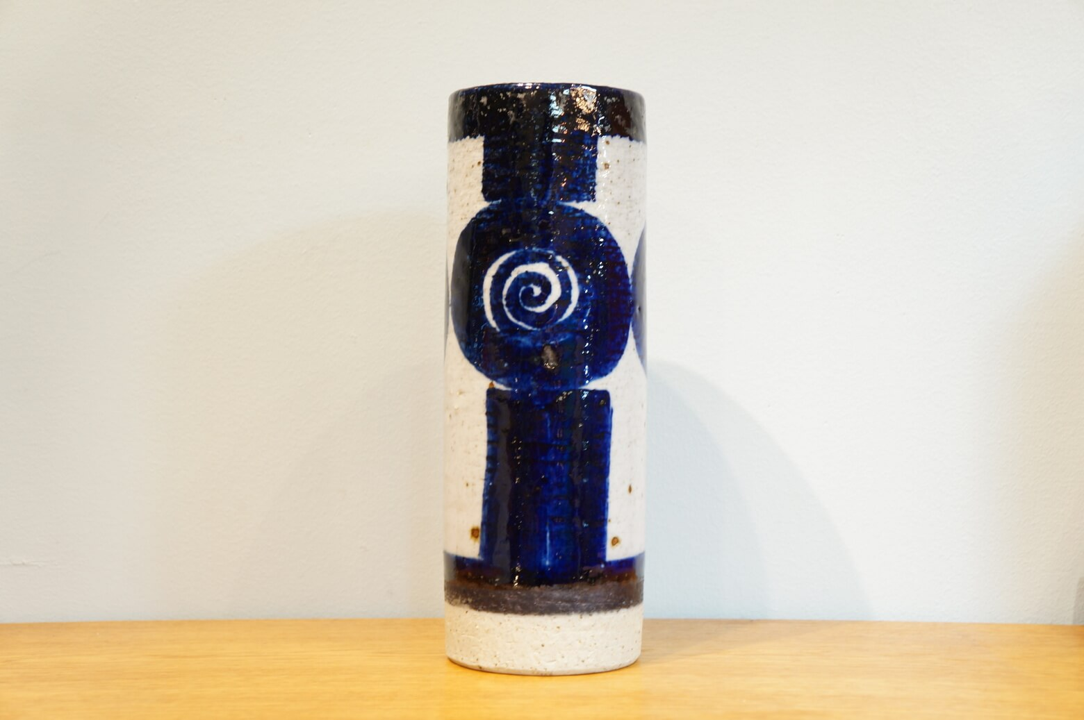 """スウェーデン出身の女性デザイナー、インガー・パーソン作のフラワーベース。 こちらはロールストランドのアート部門""""アトリエ""""で制作されました。 分厚くずっしりとした造りのベースに深みのある紺色で力強くペイントされています。 渦巻きにもお花にも見える個性的なペイントです。 ツヤのある釉薬をかけている部分と、根元のざらっとした質感を残した部分と、質感の違いも楽しめます。 存在感たっぷりのフラワーベースです。 経年による細かなスレなどございますが、ダメージのほとんどない美品です。 インガー・パーソンは1959〜1970、1981〜1996と長きにわたってロールストランドに在籍し、たくさんの作品を残しました。 丸いモチーフと青を好んだとされる彼女の作品は、まんまるい体と目がかわいらしいフクロウのフィギュリンや陶板、ターコイズブルーのような綺麗なブルーを使ったベースなどがあります。 どれも素朴でほっこり、和風なスタイルにも合わせやすいものばかりです♪ ~【東京都杉並区阿佐ヶ谷北アンティークショップ 古一】 古一/ふるいちでは出張無料買取も行っております。杉並区周辺はもちろん、世田谷区・目黒区・武蔵野市・新宿区等の東京近郊のお見積もりも!ビンテージ家具・インテリア雑貨・ランプ・USED品・ リサイクルなら古一/フルイチへ~"""