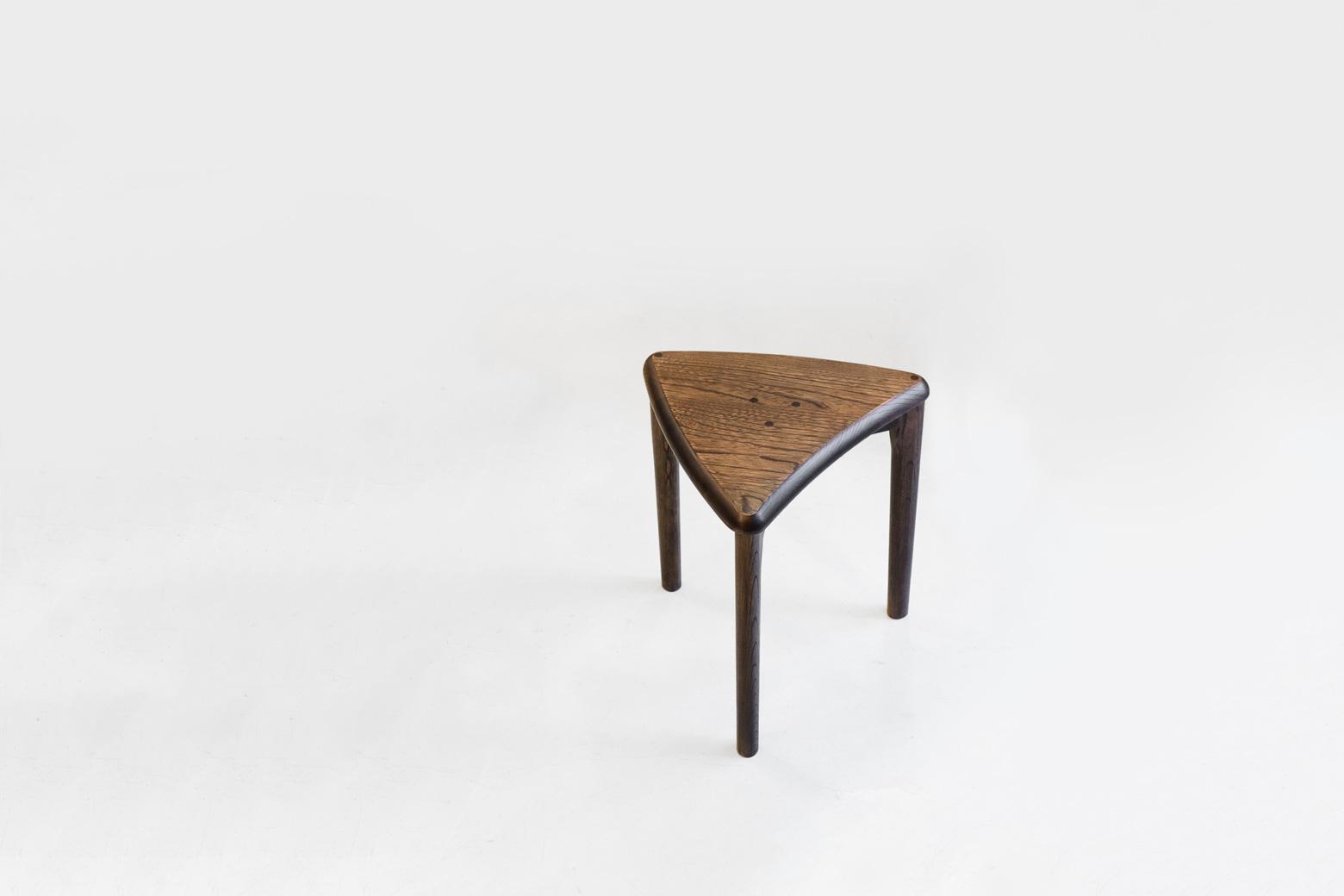 """1963年創業の家具メーカー、空間工房。 都内屈指の下町であり、また都内随一の家具・木工の町である荒川区町屋に工房を構え、腕の良い職人さんたちの卓越した技術でオリジナル家具やオーダー家具を作っています。 こちらはクルミ材を使った、おにぎりのようなかわいらしい三角形のスツール。 椅子と比べるとスツールは座り心地や安定性が劣ってしまうというウィークポイントを少しでも改善するべく、このスツールは三本脚で構成されています。 凸凹の床が多い北欧のチェアやスツールも安定性をアップさせるために三本脚のものが多くありますね。 さらに、座面の裏側を見てみると、三本の脚が""""剣留め""""という伝統的な技法で接合されており、より一層ブレにくく、歪みにくい、強度の高い構造になっています。 細かな傷やスレがございますが、大きなダメージはございません。 こちらのスツールは6脚ピタッとつけて並べると円形に、3脚並べると半円になるという、使わない時はそのまま置いておくだけでインテリアのようにもなります。 玄関で靴を履くときに座ったり、ドレッサー用に使ったり、スツールはコンパクトだから実は使い勝手も◎。 脇役のように使いがちのスツールもこれならいつでも使いたいと思わせてくれる、かわいらしいスツールです。 ~【東京都杉並区阿佐ヶ谷北アンティークショップ 古一】 古一/ふるいちでは出張無料買取も行っております。杉並区周辺はもちろん、世田谷区・目黒区・武蔵野市・新宿区等の東京近郊のお見積もりも!ビンテージ家具・インテリア雑貨・ランプ・USED品・ リサイクルなら古一/フルイチへ~"""