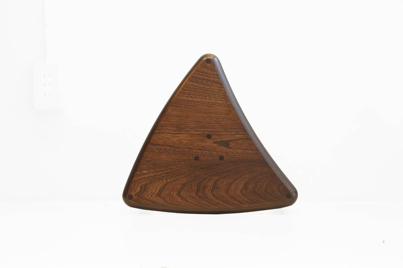 """1963年創業、東京都荒川区町屋に工房を構える家具メーカー、空間工房。 クルミ材を使った、おにぎりのような形のかわいらしい三角形のスツールです。 座面はただの三角形ではありません。 絶妙なえぐれと膨らみがあることにより、6脚並べると円形に3脚並べると半円になるという、ただ並べて置いていても絵になるような計算された形になっています。 さらに5脚まではスタッキングが可能なのでとてもコンパクトに収まります。 スツールは来客時の補助椅子として使われることが多く、使わない時は部屋の隅や押入れの中にしまわれてしまう脇役的な存在ですが、このスツールは使う時と使わない時の両方を考えられたデザイン性と実用性ともに優れた一脚です。 細かな傷やスレがございますが、大きなダメージはございません。 実は座面の裏側を見ると、""""剣留め""""という日本の伝統的な技法で三本の脚が接合されています。 この技法を使うことによって、座った時によりブレにくく、歪みにくくなっています。 たかがスツール、されどスツール… スツールは使用頻度があまり高くない家具ではありますが、こだわりのあるものであればいつでもどこでも活躍させてあげたいですよね♪ ~【東京都杉並区阿佐ヶ谷北アンティークショップ 古一】 古一/ふるいちでは出張無料買取も行っております。杉並区周辺はもちろん、世田谷区・目黒区・武蔵野市・新宿区等の東京近郊のお見積もりも!ビンテージ家具・インテリア雑貨・ランプ・USED品・ リサイクルなら古一/フルイチへ~"""