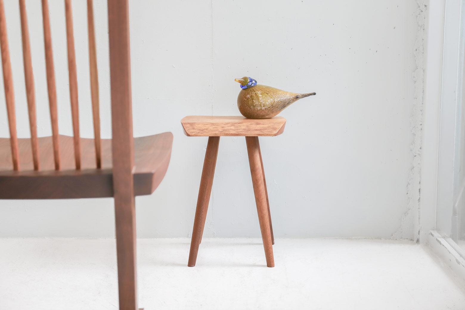 """ジョージ・ナカシマの家具を作れるのは世界中で二カ所のみ。 一つはアメリカペンシルヴェニア州ニューホープのアトリエ、そしてもう一つが香川県に工場を構える桜製作所です。 こちらはその桜製作所製のサイドテーブル。 ジョージ・ナカシマのプランクスツールやウォルテーブルをもとにデザインされたものです。 小さなテーブルながらも、無垢材のあたたかみや力強さが感じられる逸品です。 ソファやチェアのサイドテーブルとして、花瓶やインテリアを飾る小さなテーブルとして。 ぜひ、木の持つ優しさ、生命力を身近に感じてみてください。 細かなスレやキズはございますが、大きなダメージはなく、比較的綺麗な状態です。 ジョージ・ナカシマから""""木""""へのこだわりやスピリットを継承した、桜製作所創業者の永見眞一氏。 木を知り尽くした『木のマエストロ』とも呼ばれています。 90歳を超えても精力的に製作活動を続けた永見氏は2015年に亡くなるまで、生涯現役を貫きました。 ~【東京都杉並区阿佐ヶ谷北アンティークショップ 古一】 古一/ふるいちでは出張無料買取も行っております。杉並区周辺はもちろん、世田谷区・目黒区・武蔵野市・新宿区等の東京近郊のお見積もりも!ビンテージ家具・インテリア雑貨・ランプ・USED品・ リサイクルなら古一/フルイチへ~"""