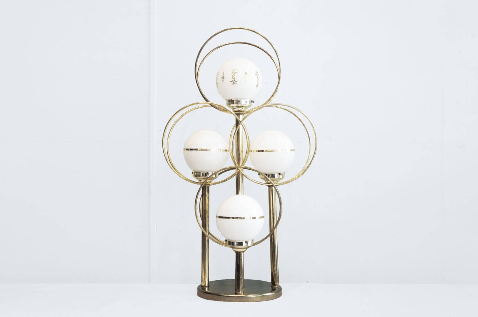 1960~70年代、アメリカ製ヴィンテージランプです。 ゴールドの輪の中に乳白色のガラスボールが浮かんでいるような不思議なルックスで、 これぞミッドセンチュリーやスペースエイジといったデザインです。 大きめなサイズ感なので、テーブルランプにもフロアランプにもお使いいただけます。 一番上のガラスシェードにはこの時代を象徴するアトミック柄のようなモチーフが施されています。 ベースに付いているスイッチをカチッと回すと、左右の2灯→上下の2灯→4灯全ての順番で切り替えることができます。 シチュエーションによって点灯する数を変えるとまた雰囲気が変わっておもしろいですよ♪ 経年や使用に伴う、細かな傷や擦れがございます。 また、フレーム、ベースに錆びがございますが、動作には問題ございません。 とにかくインパクトの強い個性的なミッドセンチュリーデザイン。 そんなインテリアが一つでもあると、なんだか古き良き時代のアメリカにタイムスリップしたような感覚になりますね。 個性的なアイテムでお部屋を彩ってみてはいかがですか? ~【東京都杉並区阿佐ヶ谷北アンティークショップ 古一】 古一/ふるいちでは出張無料買取も行っております。杉並区周辺はもちろん、世田谷区・目黒区・武蔵野市・新宿区等の東京近郊のお見積もりも!ビンテージ家具・インテリア雑貨・ランプ・USED品・ リサイクルなら古一/フルイチへ~