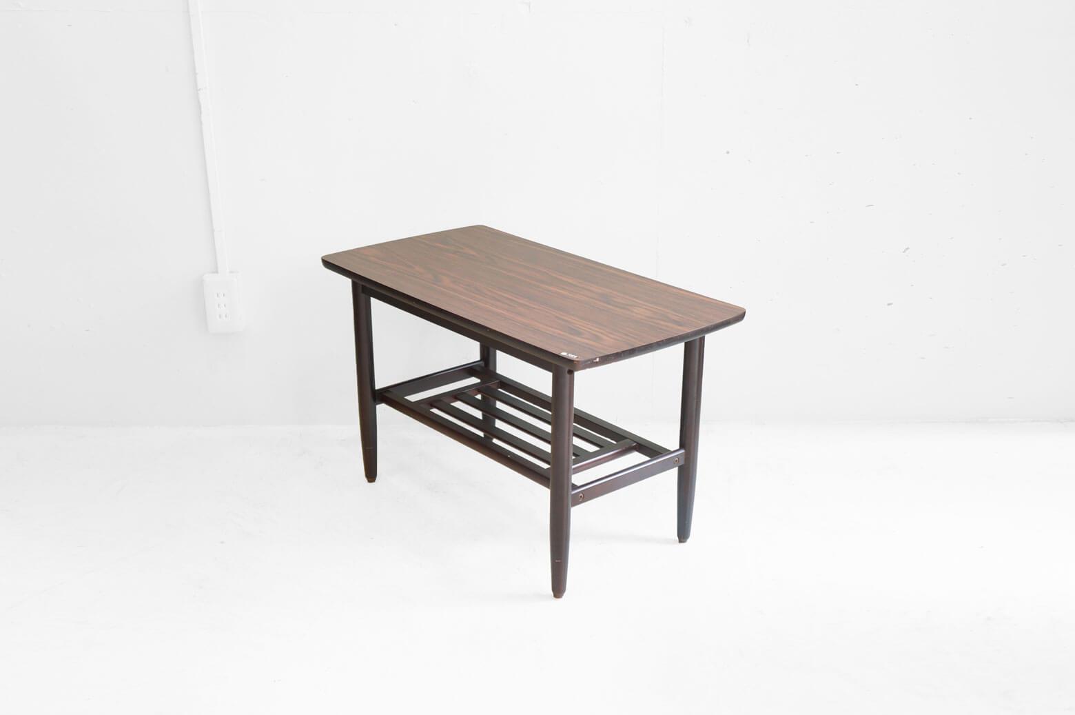 1947年創業の国産家具メーカー、カリモク。 こちらは『オールドカリモク』と呼ばれるヴィンテージのコーヒーテーブルです。 普遍的なデザインと落ち着いたローズウッドカラーが、レトロモダンな家具ともヴィンテージ家具とも、とても相性が良いです。 天板にはメラミン加工がされているため、お手入れも簡単! 雑誌やリモコン、ティッシュボックスなどを置ける棚板が付いているのもうれしいポイントです。 経年や使用に伴う、傷や擦れがございますが、大きなダメージはなく、まだまだお使いいただけます。 現行でも似たデザインのリビングテーブルが販売されていますが、ローズウッドカラーはヴィンテージのみの仕様となっています。 レトロモダンなカフェスタイルにぜひいかがでしょうか♪ ~【東京都杉並区阿佐ヶ谷北アンティークショップ 古一】 古一/ふるいちでは出張無料買取も行っております。杉並区周辺はもちろん、世田谷区・目黒区・武蔵野市・新宿区等の東京近郊のお見積もりも!ビンテージ家具・インテリア雑貨・ランプ・USED品・ リサイクルなら古一/フルイチへ~
