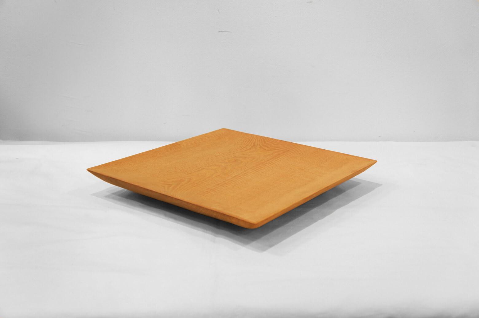 """木工デザイナー、三谷龍二さんが手掛けた四方皿。 桜の無垢材を丁寧に削り出して作られています。 シンプルな四角形の木の器ですが、無垢材の温もり、力強さが存分に感じられます。 三谷さんの作品のなかでもこちらの四方皿のように大きなサイズはとても珍しい作品です。 日常使いするのは勿体なくて飾っておきたいと思ってしまいそうですが、三谷さんが作るお皿は""""陶磁器のような普段使いできる木の器""""として作られています。 ぜひ他の食器と一緒にテーブルに並べてお使いください。 裏に汚れがございます。 また、経年や使用に伴い、製作当時よりも表面の色合いが変化していると思われます。 使っていくごとに増していく木の深い味わいをお楽しみください。 三谷さんの繊細な手仕事が感じられる作品はとても人気が高く、個展を開くと行列ができて作品はすぐに完売してしまうのだとか… お探しの方はぜひお見逃しなく! ~【東京都杉並区阿佐ヶ谷北アンティークショップ 古一】 古一/ふるいちでは出張無料買取も行っております。杉並区周辺はもちろん、世田谷区・目黒区・武蔵野市・新宿区等の東京近郊のお見積もりも!ビンテージ家具・インテリア雑貨・ランプ・USED品・ リサイクルなら古一/フルイチへ~"""