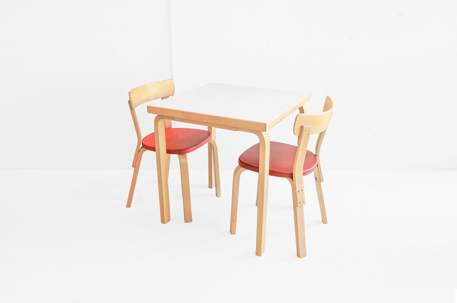 """Art(芸術)とTechnology(技術)の融合、artek/アルテック。 1935年にフィンランドで誕生したアルテックの創業者のひとりに建築家のAlvar Aalto/アルヴァ・アアルトがいます。 特徴的な曲線を描くデザイン。 自然と共存できるようなオーガニックなデザイン。 シンプルな美しさだけでなく、何十年も使い続けられるような丈夫な構造を持つアアルトの作品はまさにアルテックの名前の由来通り。 今回はアアルトの代名詞""""Lレッグ""""を使用した二人掛けダイニングテーブルとチェアNo.69をセットでご提案します。 1973~80年製のものと思われる、ホワイトのリノリウム天板を使用ダイニングテーブルは現行品よりも少し小さめでヴィンテージでしか出会えないサイズ。 アアルトの定番ダイニングチェアNo.69、座面には赤いビニールレザーが張られています。 それぞれ1950~65年製、1965~73年製のものと思われる二脚です。 私たち日本人にはなんだかめでたく感じる""""紅白""""の組み合わせも、 フィンランドの伝統的なバーチ材が放つ落ち着きやアアルトの描いた曲線のやわらかさが加わるとしっくりと空間に馴染むダイニングセットになる。 小回りの利くコンパクトなテーブルとチェアのセットは、限られた狭い空間の中で暮らす私たちにぴったりの""""ジャパニーズ・トーキョー・サイズ""""、とでも言いましょうか… ヴィンテージ品のため、経年や使用に伴うキズやスレ、打痕などのダメージがございますが、使用に問題はございません。 No.69チェアはナチュラルな木の座面や塗装された座面、ファブリックの座面など様々なタイプがありますが、こちらのビニールレザーはお手入れがラクな点でもオススメです。 60年以上も前に作られたものが今まで使い続けられてきて、さらにこれからもまだまだ永く使える。 これもアアルトのデザインの凄いところですね。 ~【東京都杉並区阿佐ヶ谷北アンティークショップ 古一】 古一/ふるいちでは出張無料買取も行っております。杉並区周辺はもちろん、世田谷区・目黒区・武蔵野市・新宿区等の東京近郊のお見積もりも!ビンテージ家具・インテリア雑貨・ランプ・USED品・ リサイクルなら古一/フルイチへ~"""