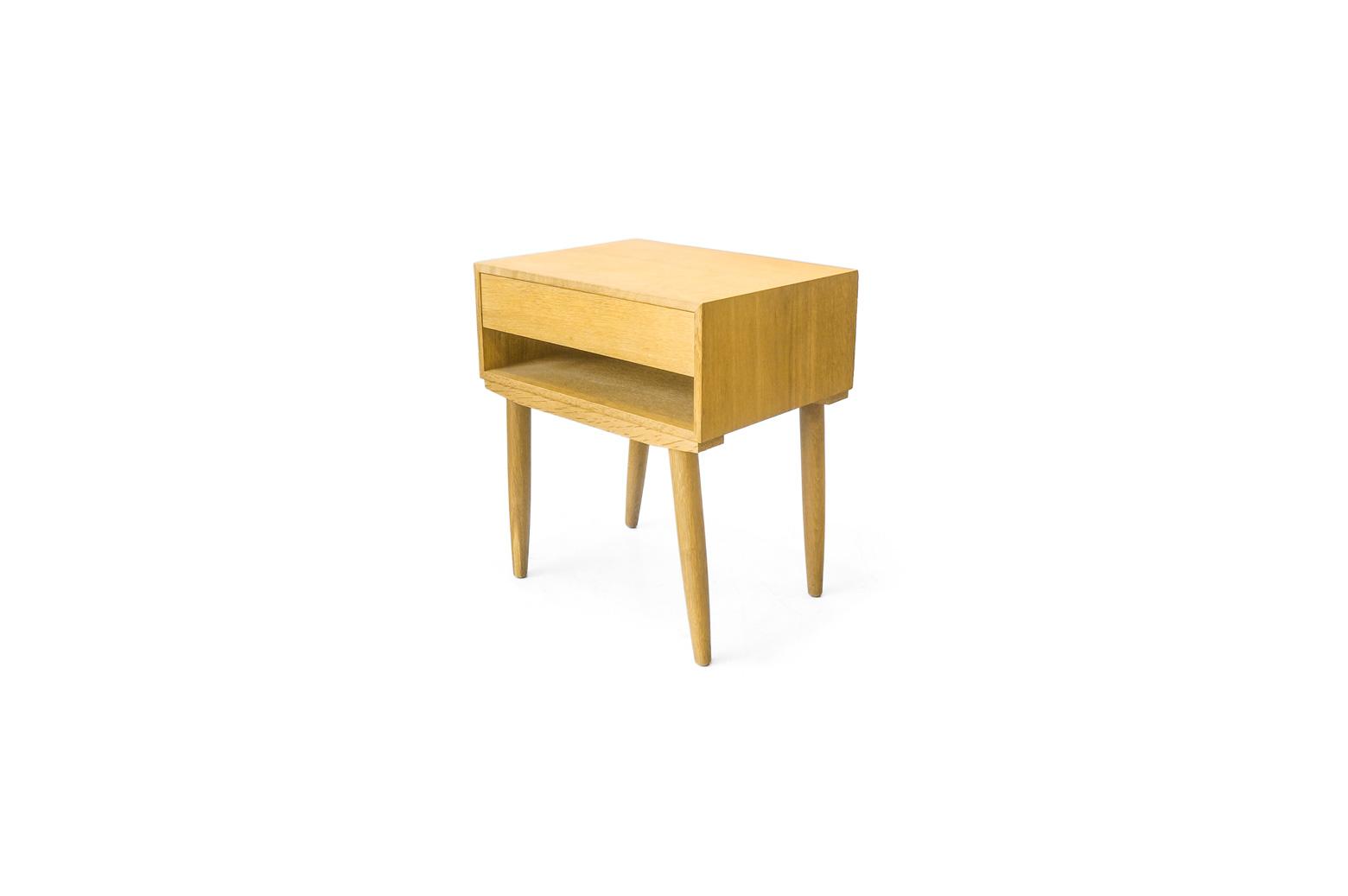 明るくナチュラルな雰囲気を味わえるオーク材を使ったベッドサイドチェスト。 取っ手を省いたフラットな面の引き出しがとてもすっきりとした印象を与えてくれます。 ハンス・J・ウェグナーのデザインでもオーク材を使ったシンプルなベッドサイドチェストがありますが、それよりもさらにシンプルさを極めたデザインになっています。 ナチュラルでコンパクトでシンプル、こんな三拍子が揃ったアイテムですから、どんなお部屋にも合わせやすく、使いやすいのは間違いないですよね。 ベッドやソファの隣や窓際、玄関などにちょこんと置いてお使いください♪ ヴィンテージ品のため、経年や使用に伴う細かな傷や擦れがございますが、大きなダメージはなく比較的良好なコンディションです。 引き出し下のオープンスペースは読みかけの雑誌やテーブル周りで行き場のなくなるリモコンなどをサッとしまえる便利なスペースです。 更に、なんと13インチのノートPCがぴったり収納できます。 天板部分にはお気に入りの花瓶などの小物をディスプレイして、引き出しには細々した物の収納に。 ちょっと狭いワンルームのお部屋でも使い方次第で、空間を有効活用できちゃいますね♪ ~【東京都杉並区阿佐ヶ谷北アンティークショップ 古一】 古一/ふるいちでは出張無料買取も行っております。杉並区周辺はもちろん、世田谷区・目黒区・武蔵野市・新宿区等の東京近郊のお見積もりも!ビンテージ家具・インテリア雑貨・ランプ・USED品・ リサイクルなら古一/フルイチへ~