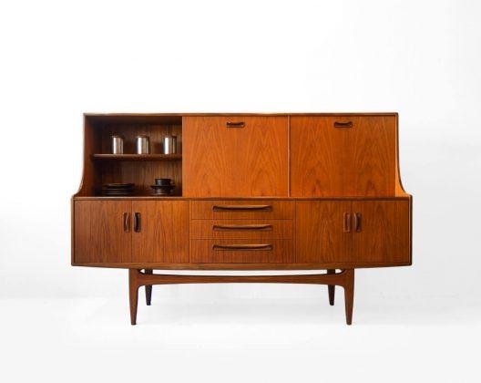 """イギリスミッドセンチュリー家具を代表するブランド、G-PLAN/ジープラン。 G-PLANの親会社、E.Gomme社の創業者の孫であるドナルド・ゴムの『シンプルでモダンな家具を作りたい』という発案から1953年に生まれました。 当時より大変人気が高かった北欧家具のエッセンスを取り入れるべく、「エリザベスチェア」で知られるデンマーク人デザイナー、イブ・コフォード・ラーセンを専属デザイナーとして起用しました。 こちらの""""フレスコ""""シリーズも彼が手掛けたもので、G-PLANのロングセラーシリーズとなりました。 イブ・コフォード・ラーセンがブランドを離れた後は、彼と並びG-PLANを代表する名デザイナーであった、ビクター・ブラムウェル・ウィルキンスがシリーズのデザインを引き継ぎました。 こちらのサイドボードの魅力はなんといっても、良質なチーク材が作りだす美しい杢目。 特徴的な杢目が左右対称になるように配置されており、思わずその綺麗さにうっとりしてしまうほど。 サイドボードの上にカップボードが乗っているようなデザインで使い勝手がよく、食器にカトラリーに小物に雑誌に本に書類に…とさまざまな物がこれ一台に収納できてしまいます。 さらに注目していただきたいのが、上段左側の扉。実は手前に引いて開ける扉ではなく、スライド扉になっています。 こんなアッと驚く意外な仕掛けも面白いですよね。 申し分のない収納力と高いデザイン性を兼ねそろえたサイドボードはリビングやダイニングの主役にぴったりです。 古いオイルを洗い落とし、新しいオイルでメンテナンスしました。 ヴィンテージ品のため、使用や経年による細かな傷や擦れ、削れがございます。 上段中央部分に日焼け、天板に輪染みが数か所ございます。 側面の一部に補修跡がございます。 使用に差し支えるような大きなダメージはなく、まだまだ永くお使いいただけます。 G-PLANの卓越した技術で作り上げられた至極の逸品。 お部屋の""""顔""""となるサイドボードはぜひ、飽きが来なく、永く使えるものをお選びくださいませ。 ~【東京都杉並区阿佐ヶ谷北アンティークショップ 古一】 古一/ふるいちでは出張無料買取も行っております。杉並区周辺はもちろん、世田谷区・目黒区・武蔵野市・新宿区等の東京近郊のお見積もりも!ビンテージ家具・インテリア雑貨・ランプ・USED品・ リサイクルなら古一/フルイチへ~"""